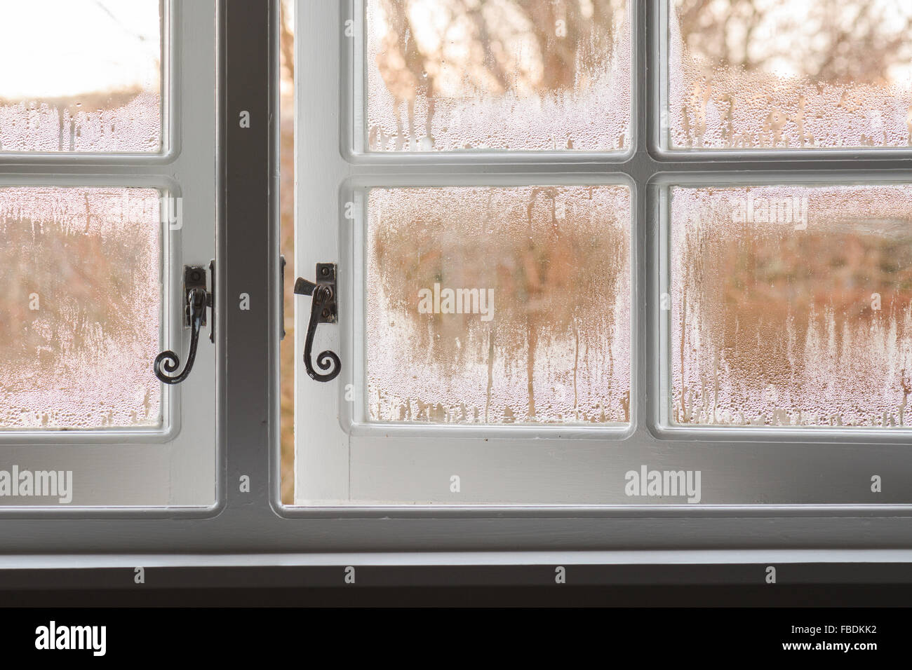 condensation running down traditional single glazed wooden windows in winter  which have been opened - Scotland, - Stock Image