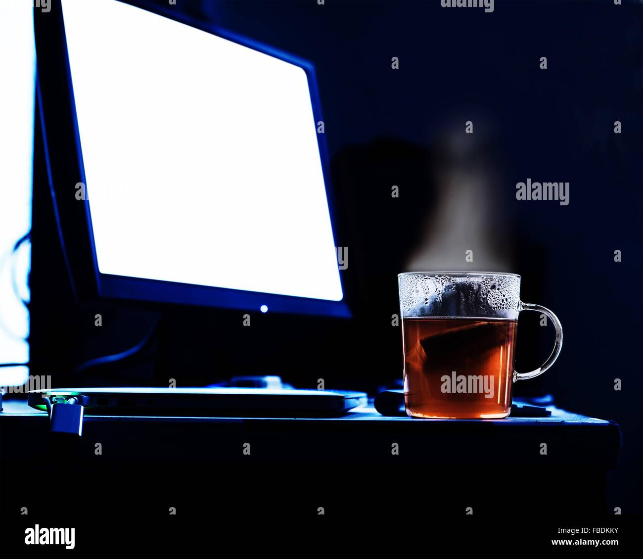 Close-Up Of Fresh Tea By Computer Monitor On Desk - Stock Image