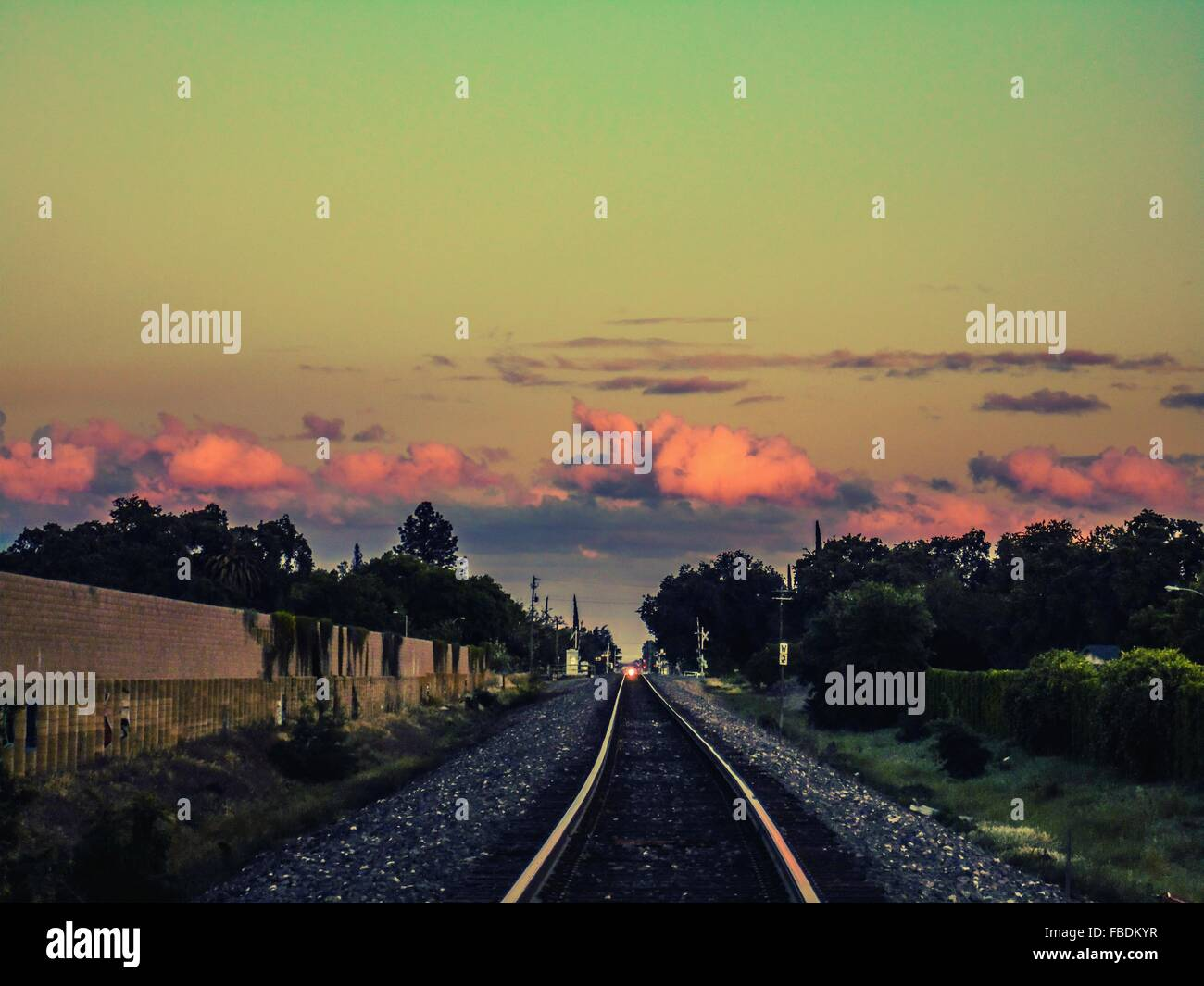 Railroad Track On Field Against Sky At Sunset - Stock Image