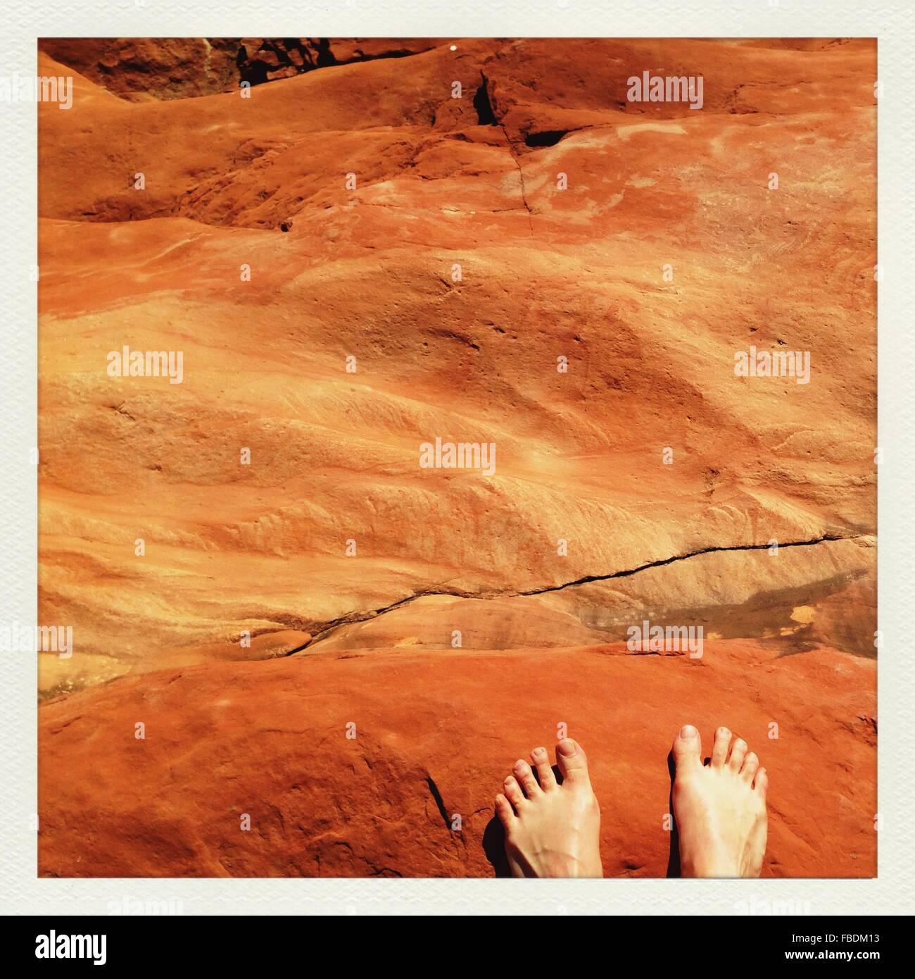 Feet Of Man On Rocks - Stock Image