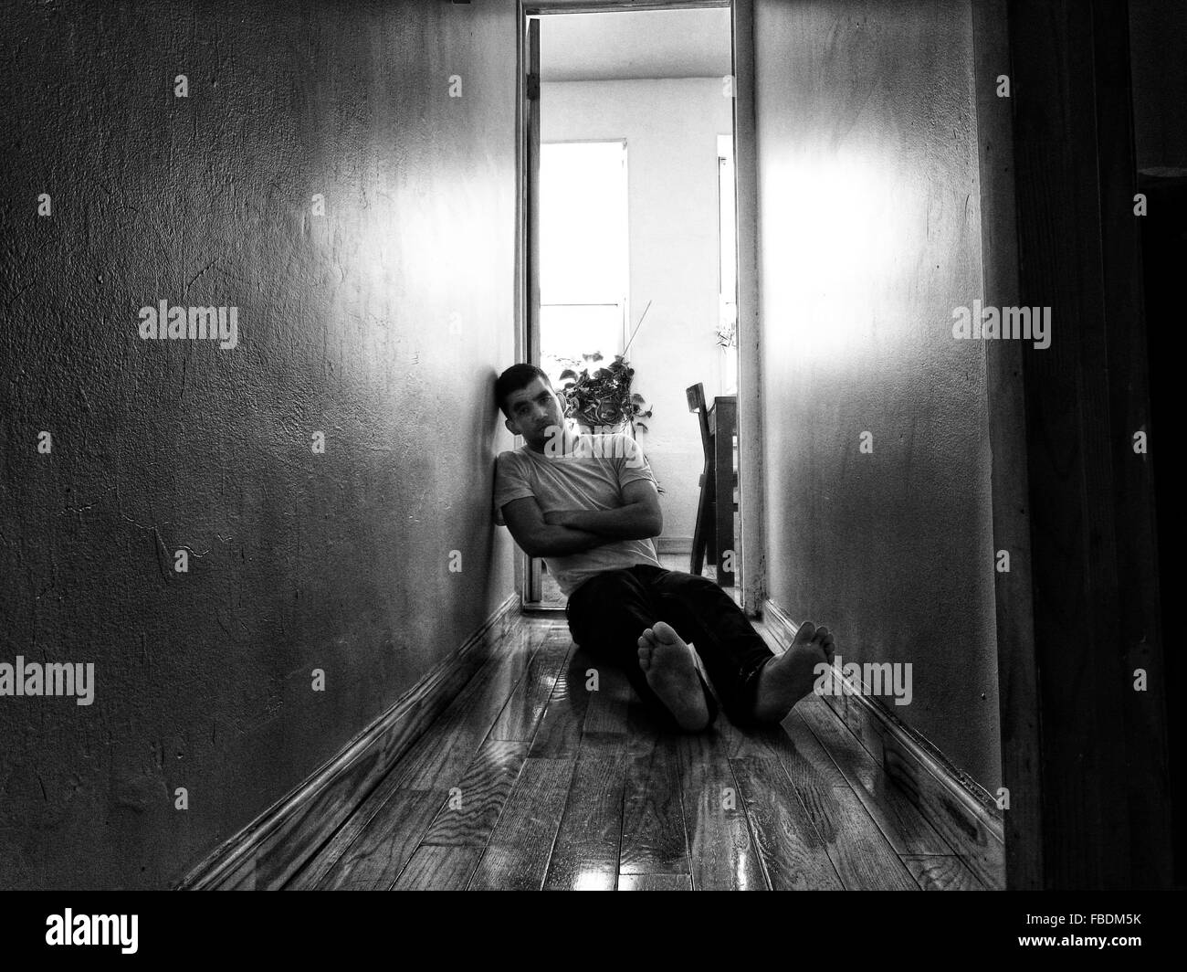 Depressed Young Man Sitting On Floor - Stock Image