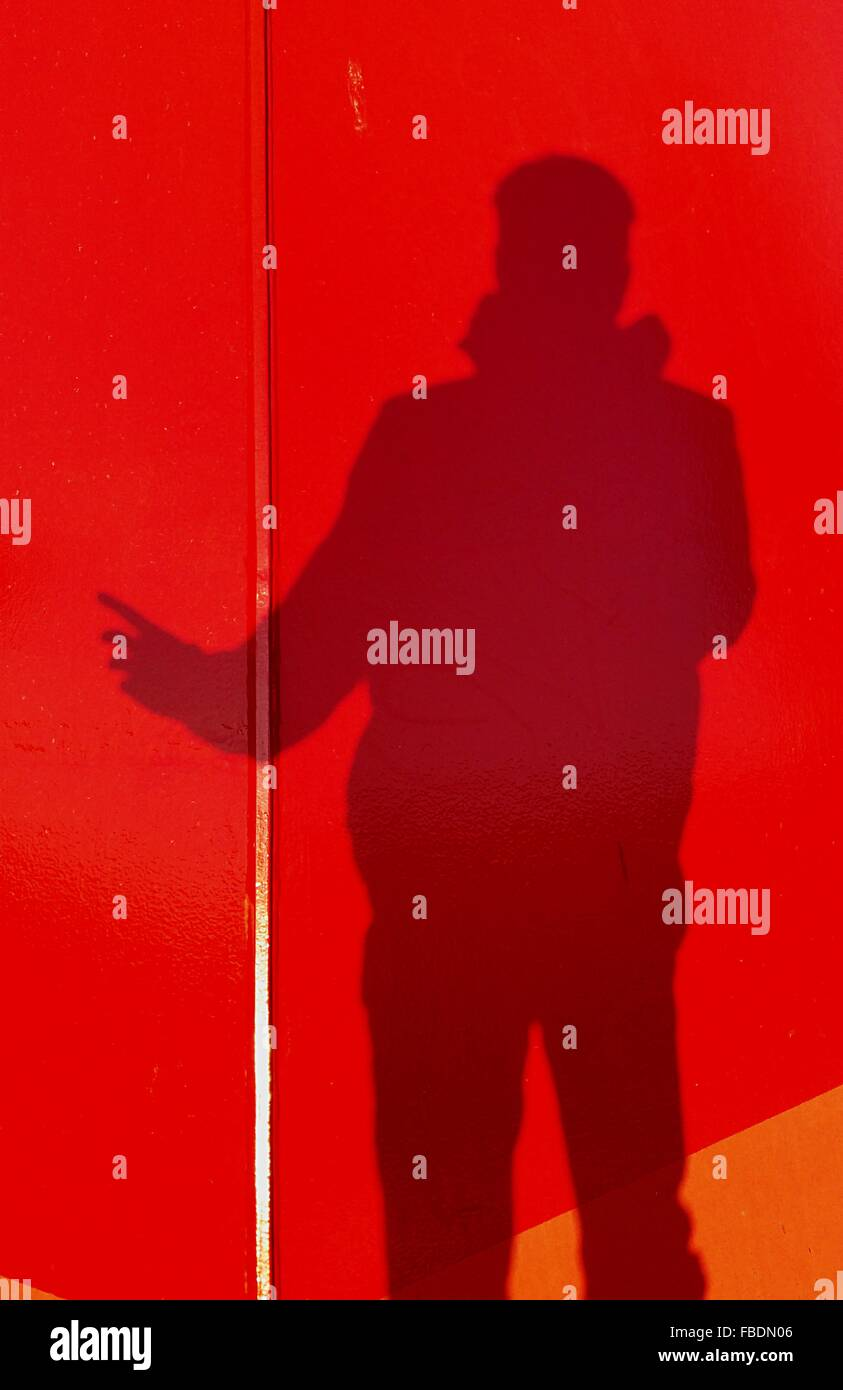 Shadow Of Person On Red Wall - Stock Image