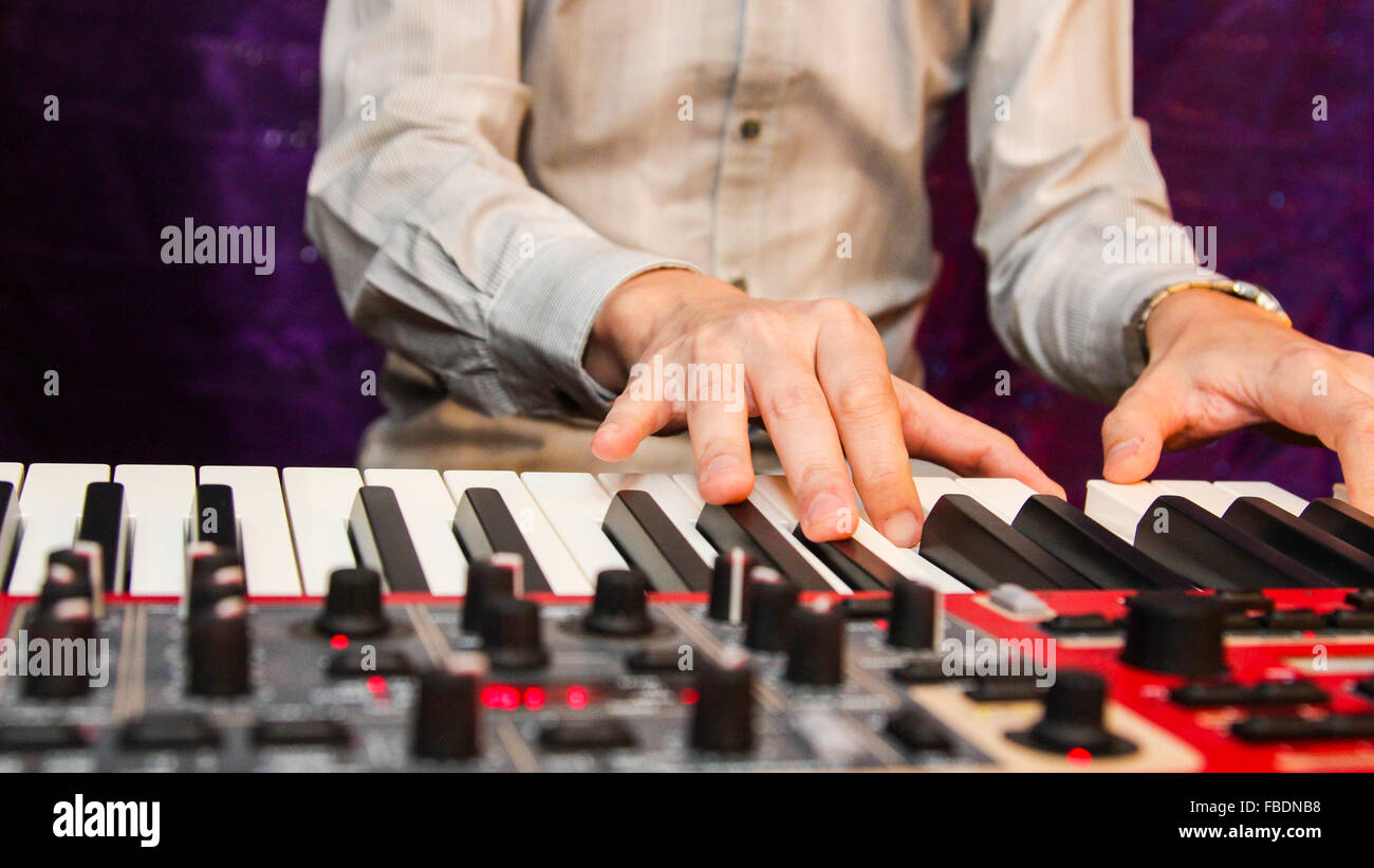 Close-Up Of Mans Hands Playing Piano - Stock Image