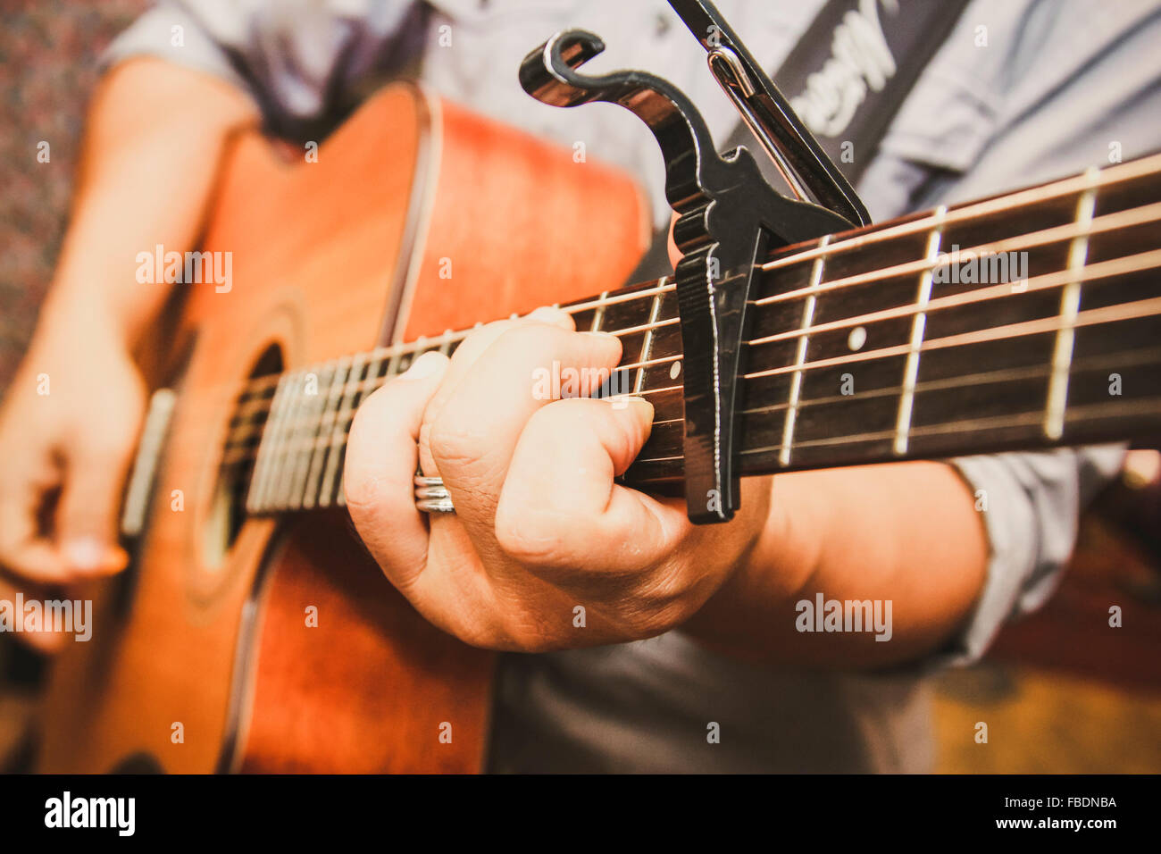 Close-Up Of Mans Hands Playing Guitar - Stock Image