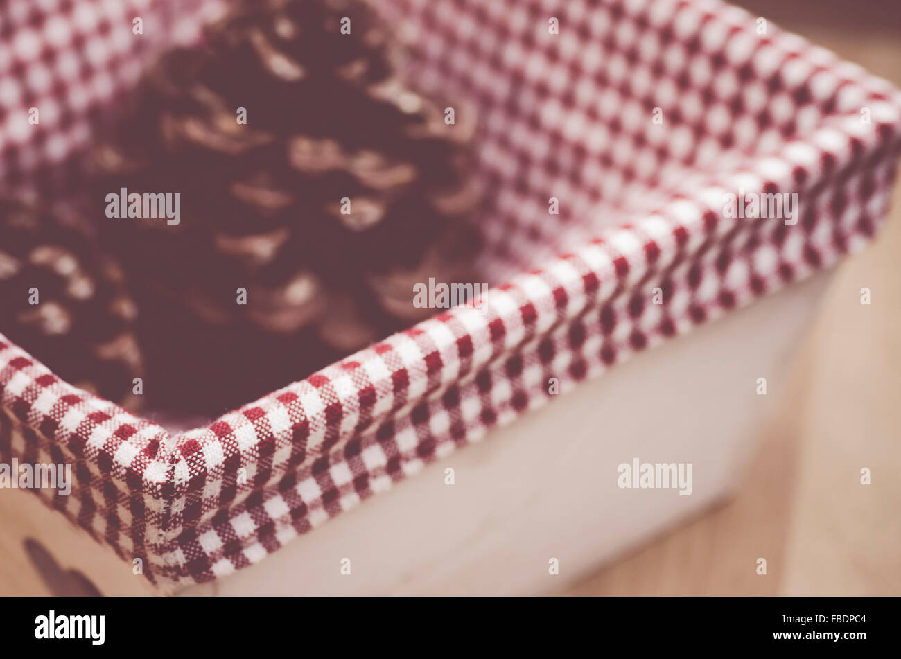 wood basket with conifer stone pine cones and checkered fabric lining - Stock Image
