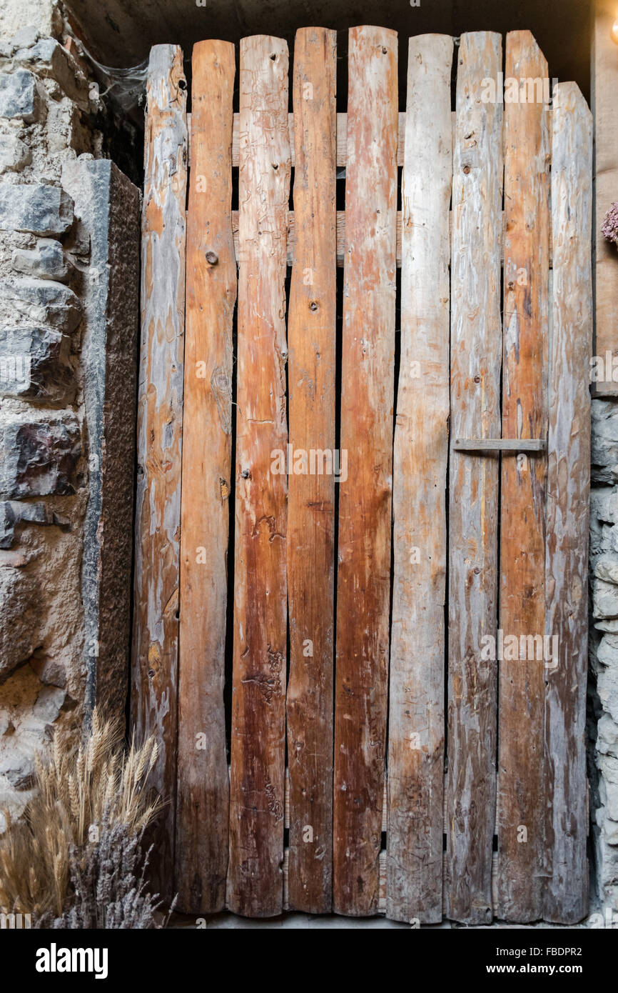 Old door made from rough planks of wood put together vertically. - Stock Image