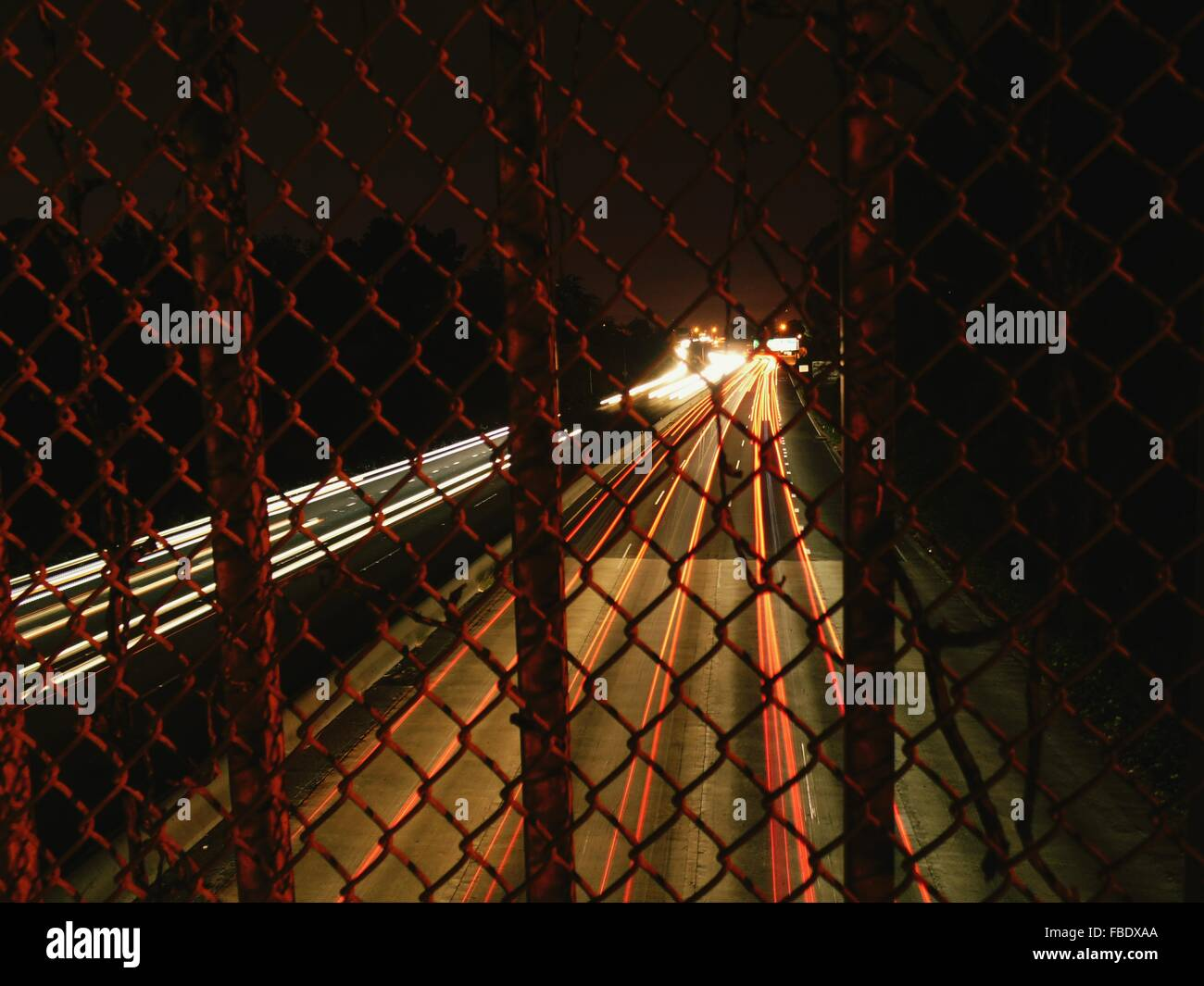 Illuminated Vehicle Light Trails On Highway Seen From Chainlink Fence - Stock Image