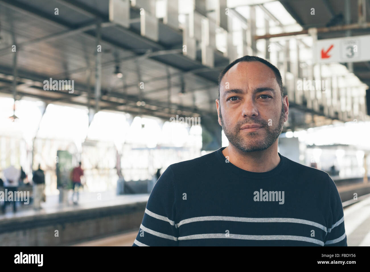 Portrait Of Mid Adult Man Standing On Railroad Station Platform - Stock Image