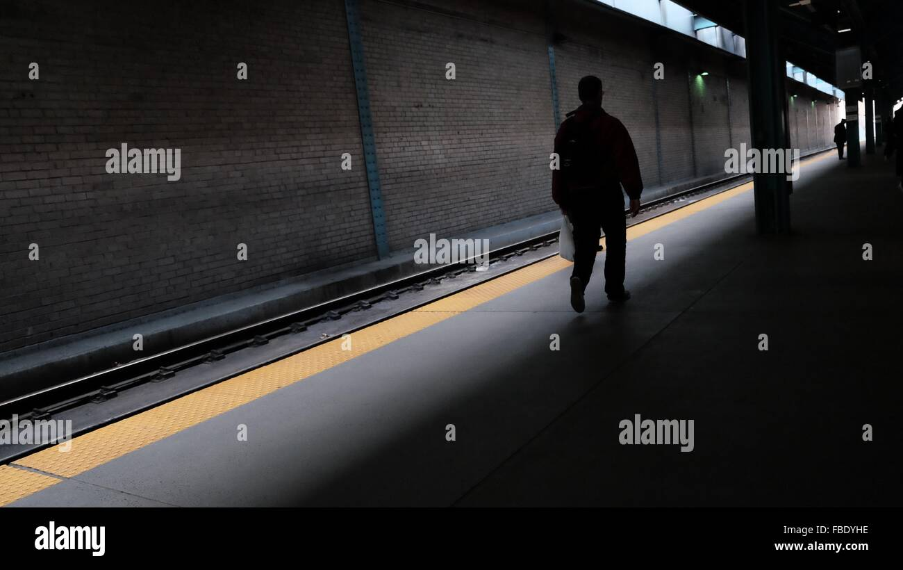 Rear View Of Man Walking On Railroad Station Platform - Stock Image