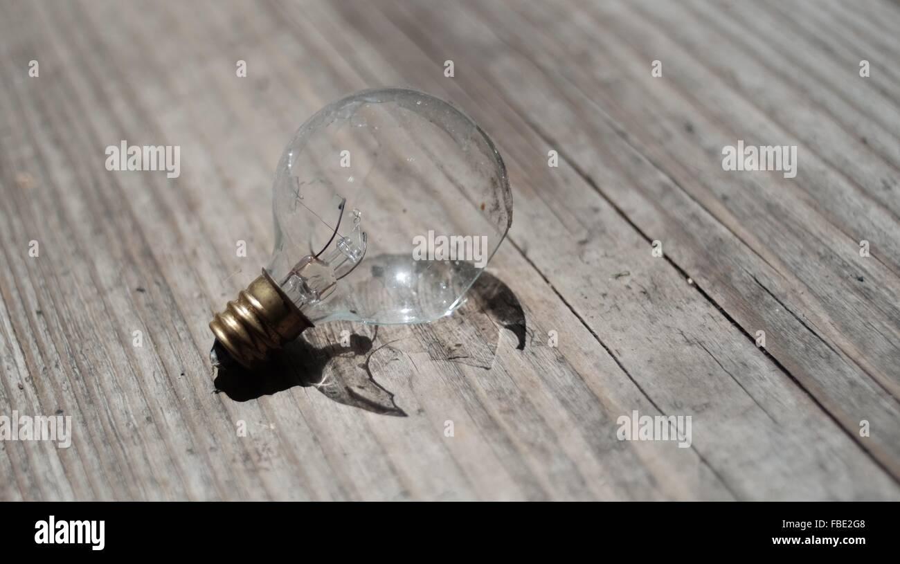 High Angle View Of Damaged Light Bulb On Hardwood Floor - Stock Image