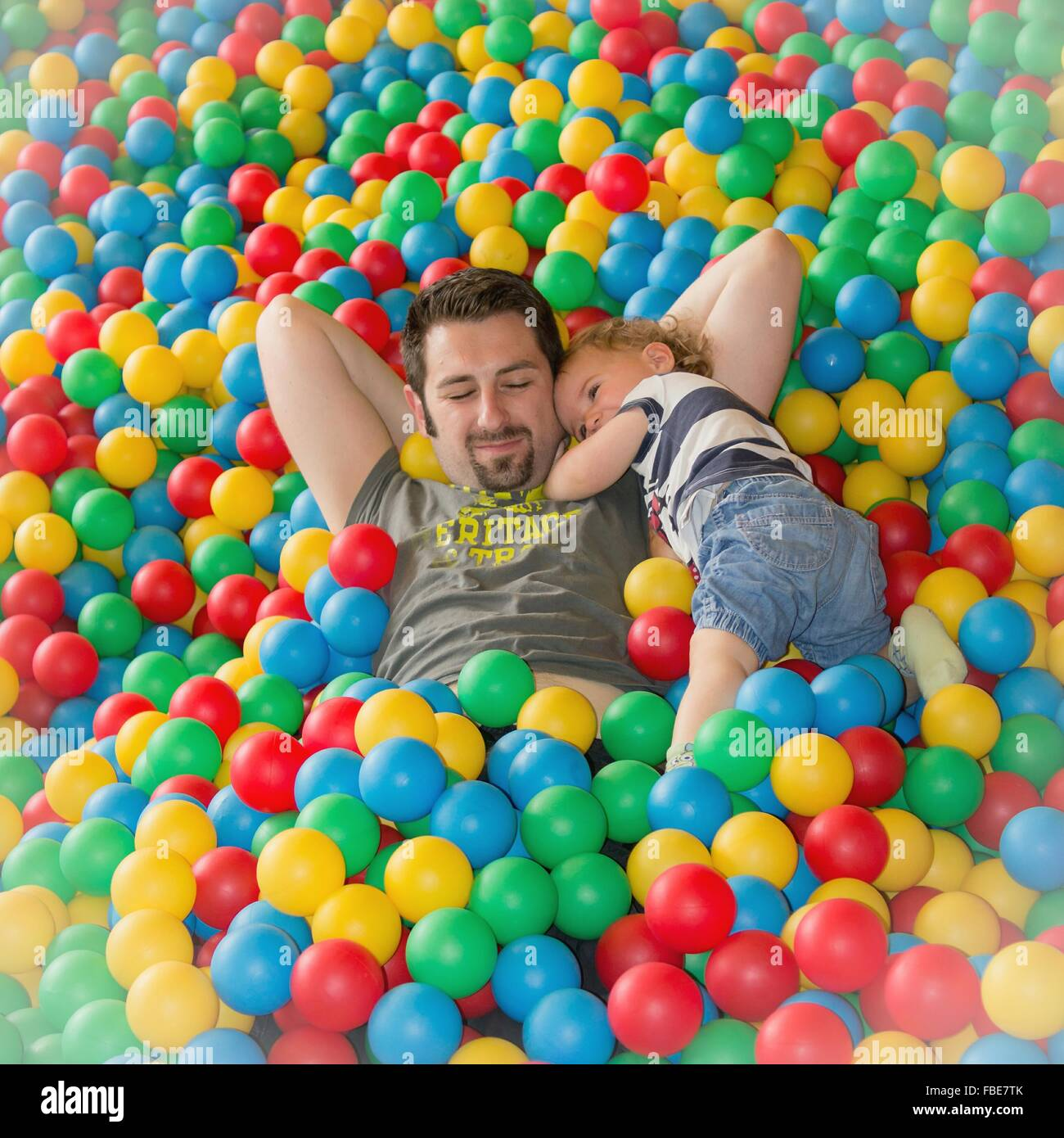 Father Lying In Balls With Son - Stock Image