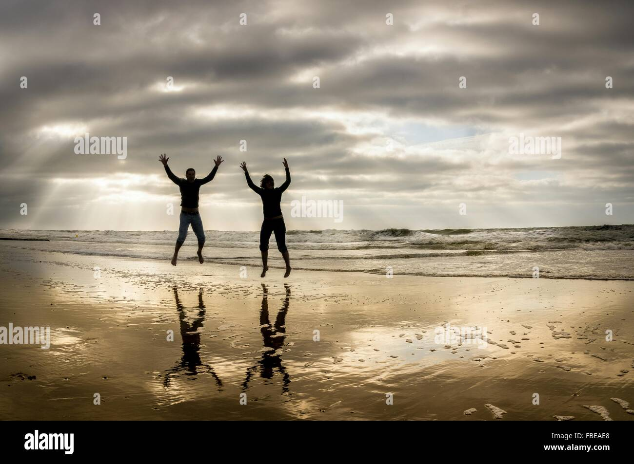 Silhouette Man And Woman With Arms Raised Jumping At Beach - Stock Image