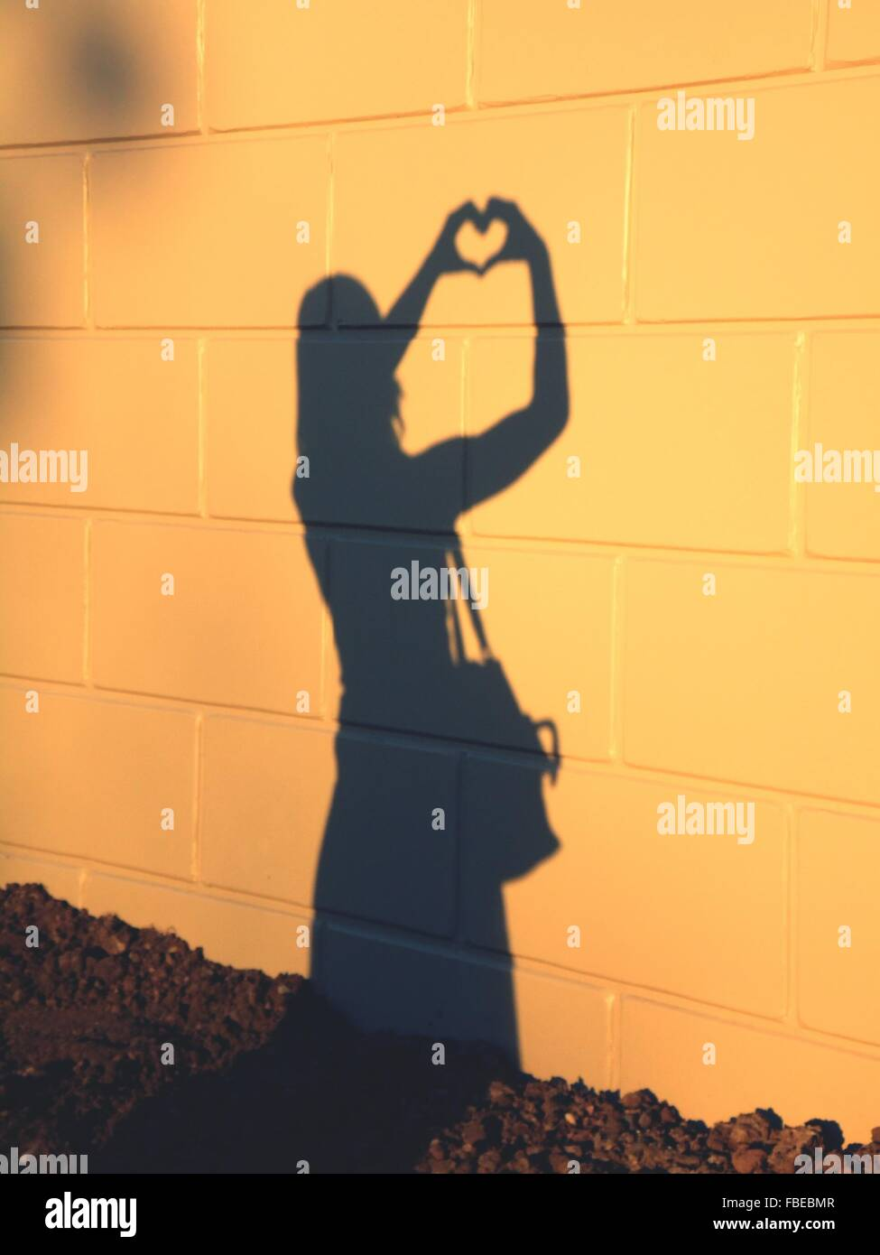 Shadow Of Woman Forming Heart On Tiled Wall - Stock Image
