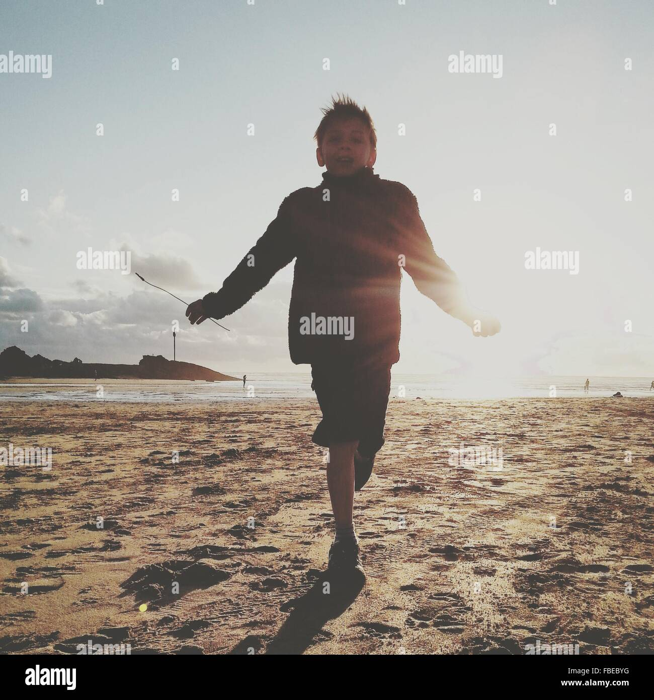 Low Angle View Of Boy Running On Beach Against Sky During Sunny Day - Stock Image