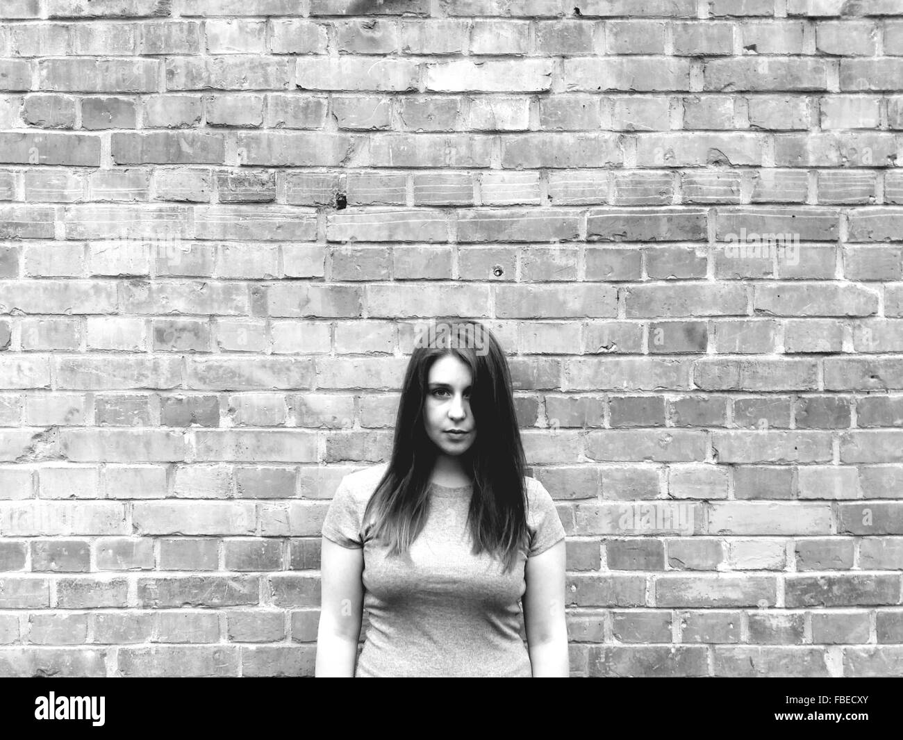 Portrait Of Woman Standing Against Brick Wall - Stock Image