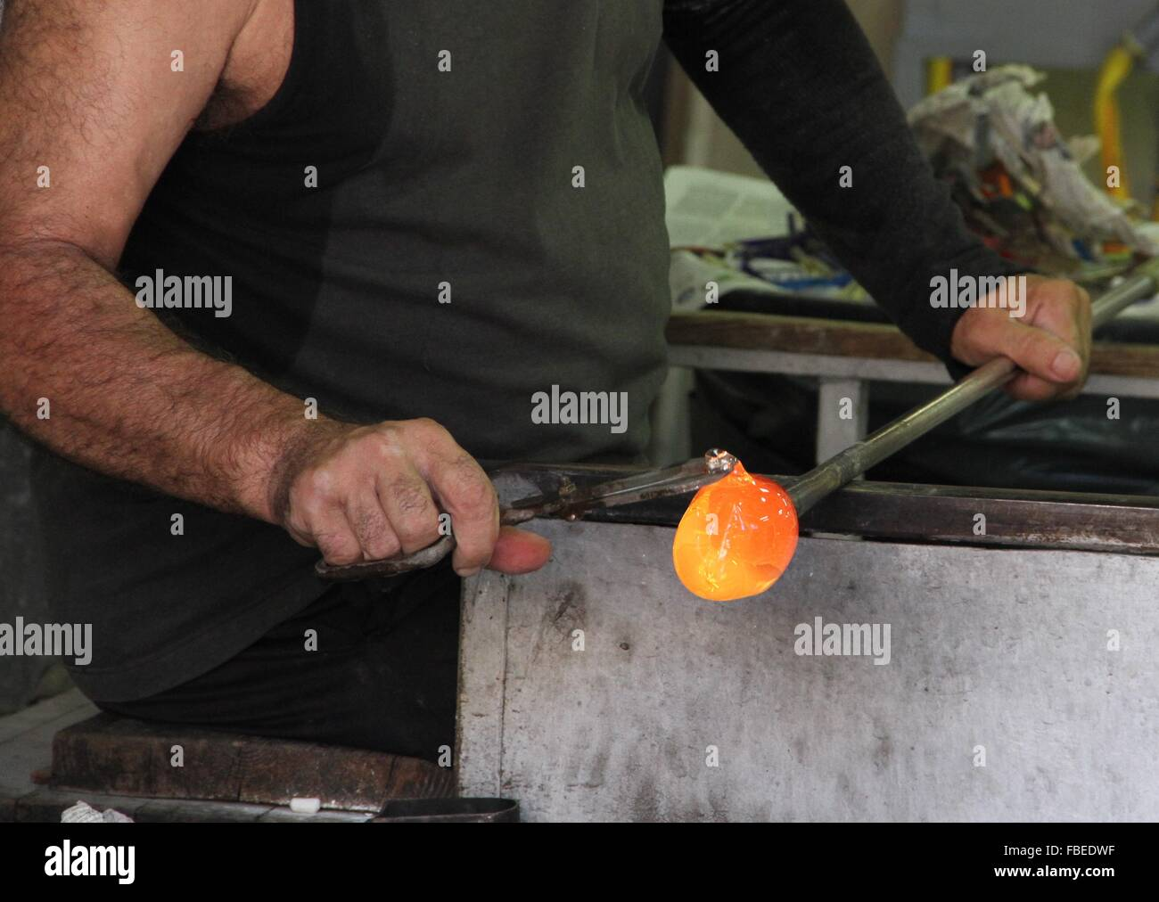 Manual Worker Holding Glass Blower In Glass Factory - Stock Image