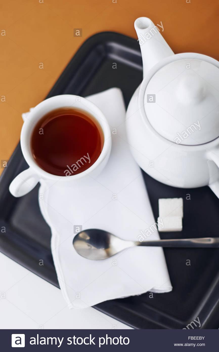 Cup of black tea and tea pot - Stock Image