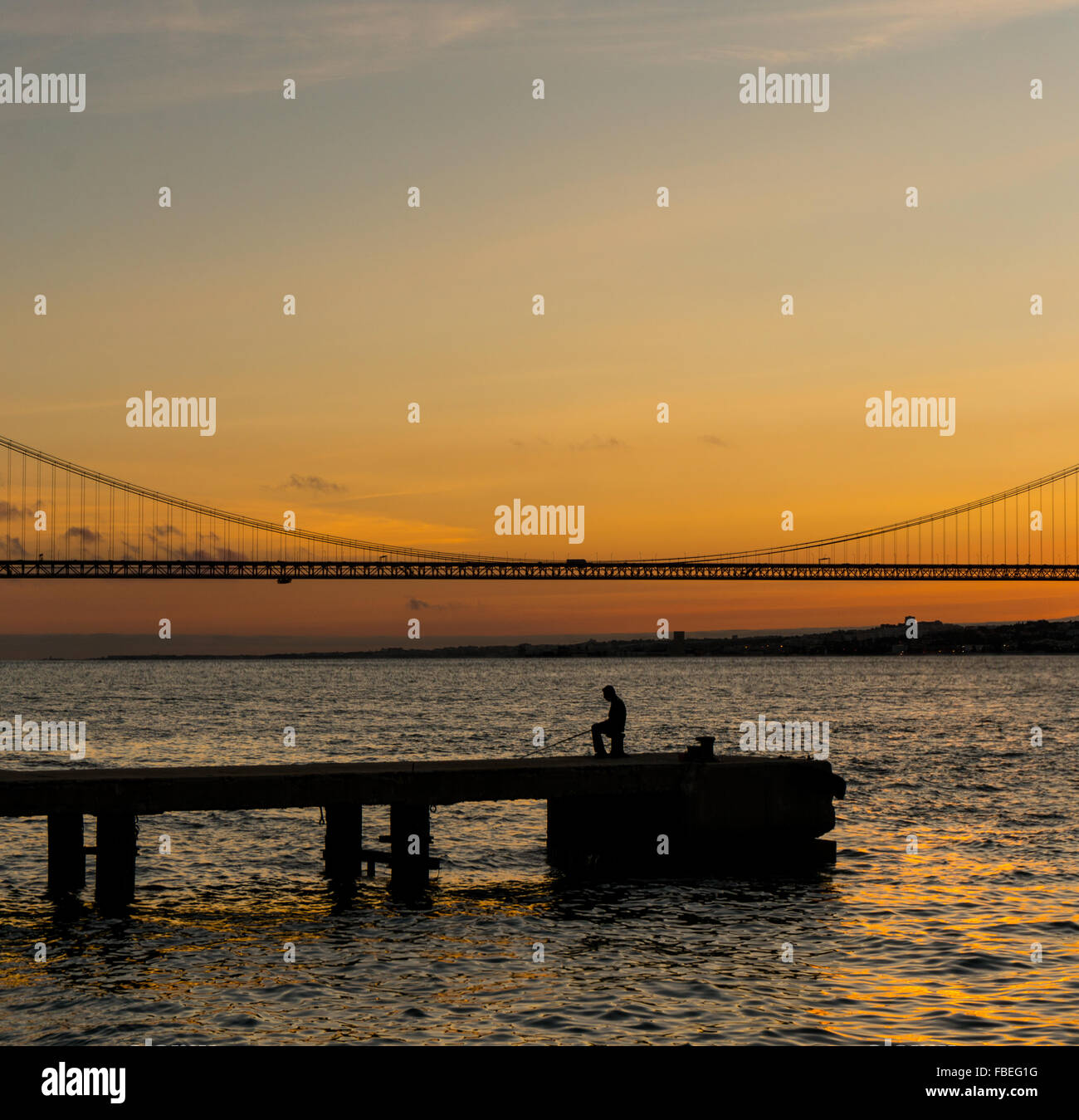 Silhouette Man On Pier Over Tagus River Against Sky During Sunset Stock Photo