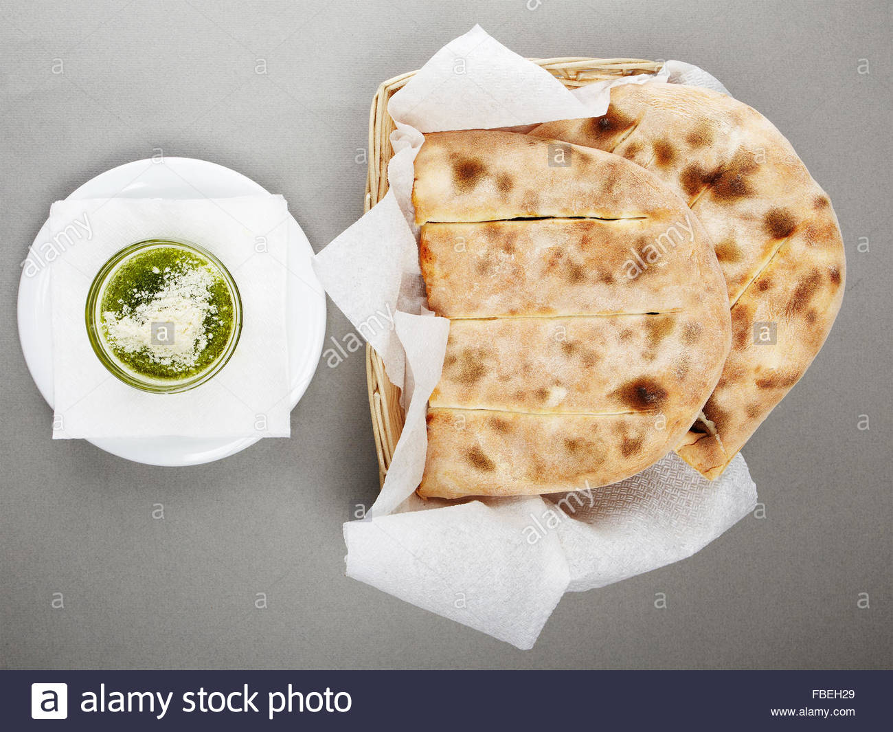 Chiabatta and pesto on grey background from above - Stock Image