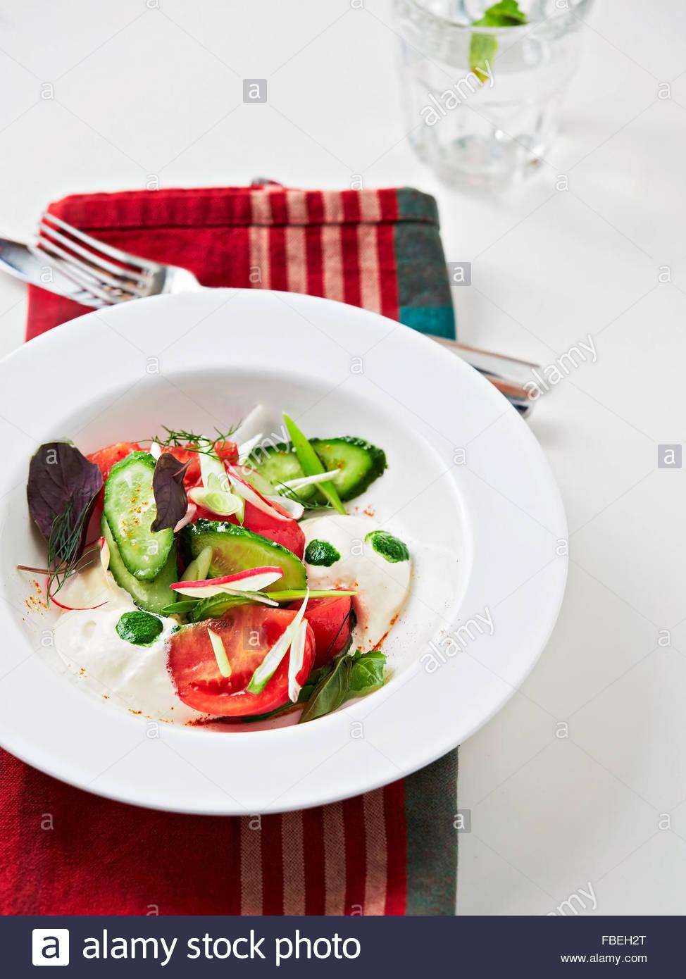 Fresh salad with cucumber, basil, tomatoes - Stock Image