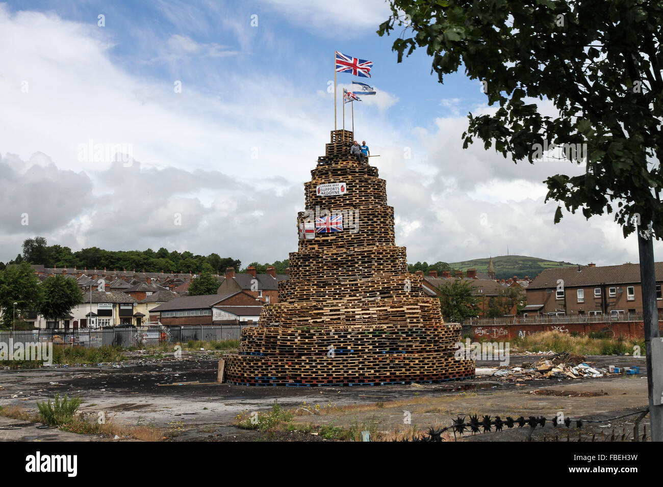 Bonfire. Flags flying on a loyalist bonfire in Belfast, Northern Ireland. This bonfire is made from wooden pallets, - Stock Image