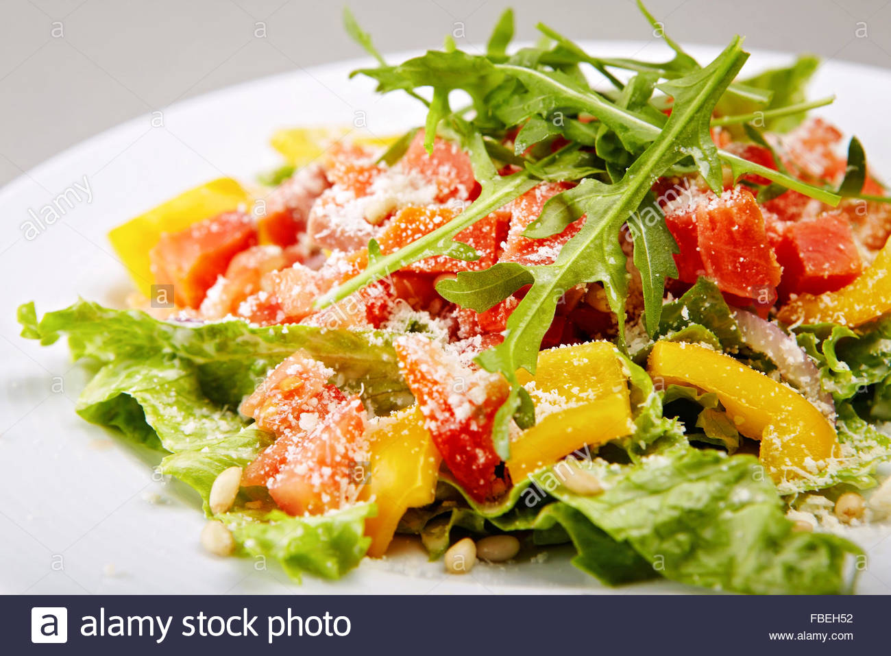 Stylised healthy salad with mixed greens, smoked salmon, tomatoes and paprica. Lots of copyspace - Stock Image