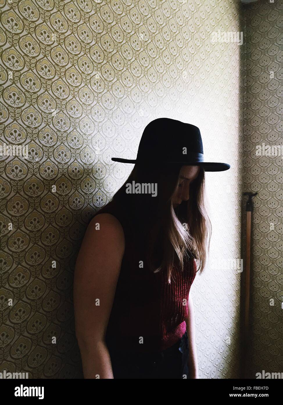 Side View Of Woman In Hat Standing Against Wall While Looking Down - Stock Image