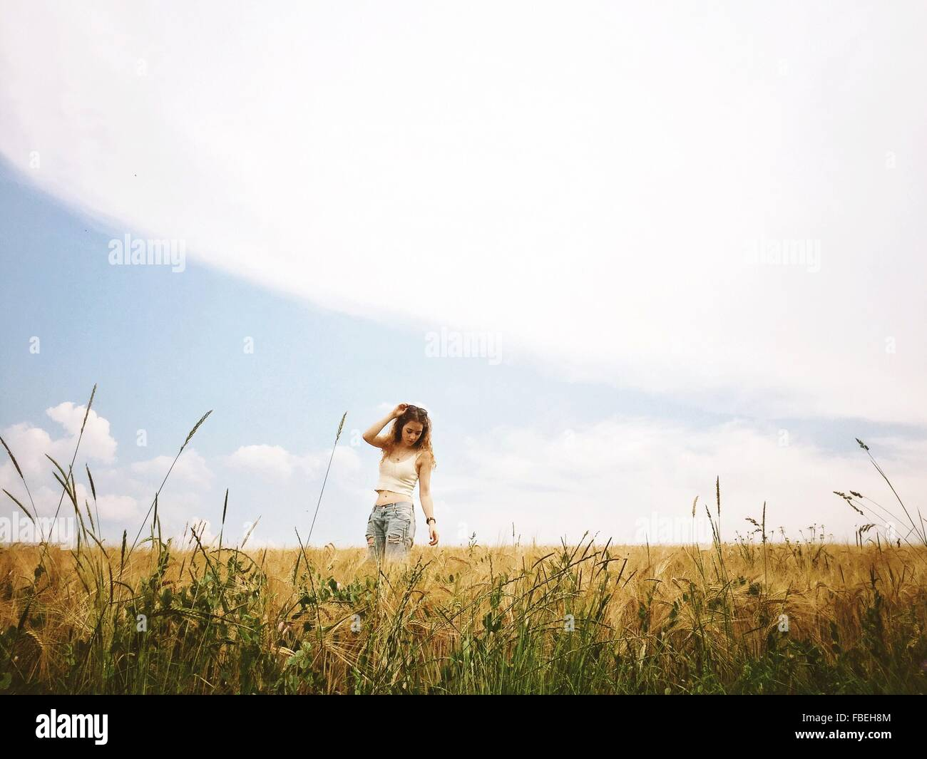 Young Woman Standing On Wheat Field - Stock Image