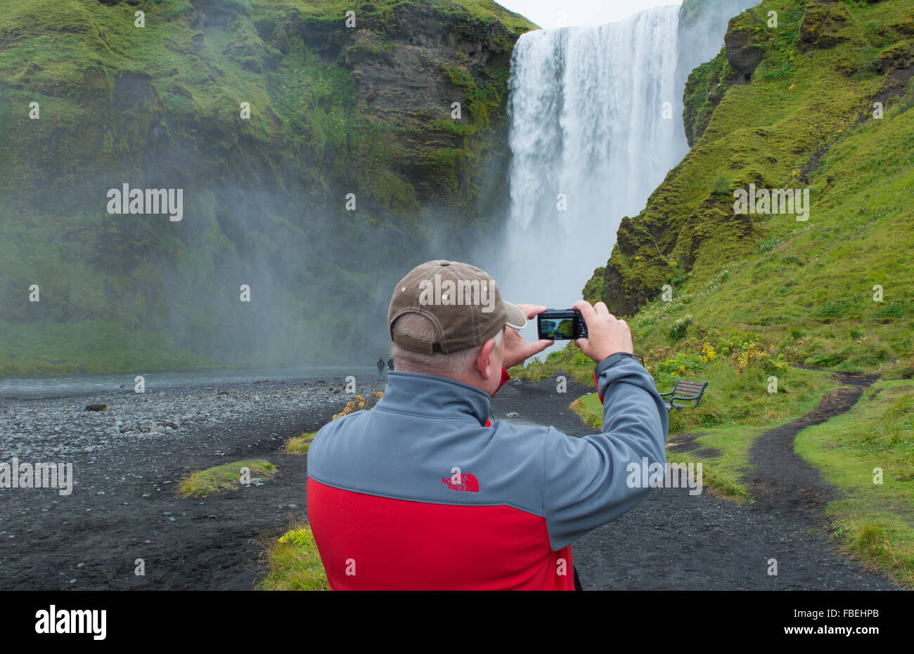 Iceland Skogafoss Waterfall famous falls in South Iceland at the Skoga River with tourists taking photos - Stock Image