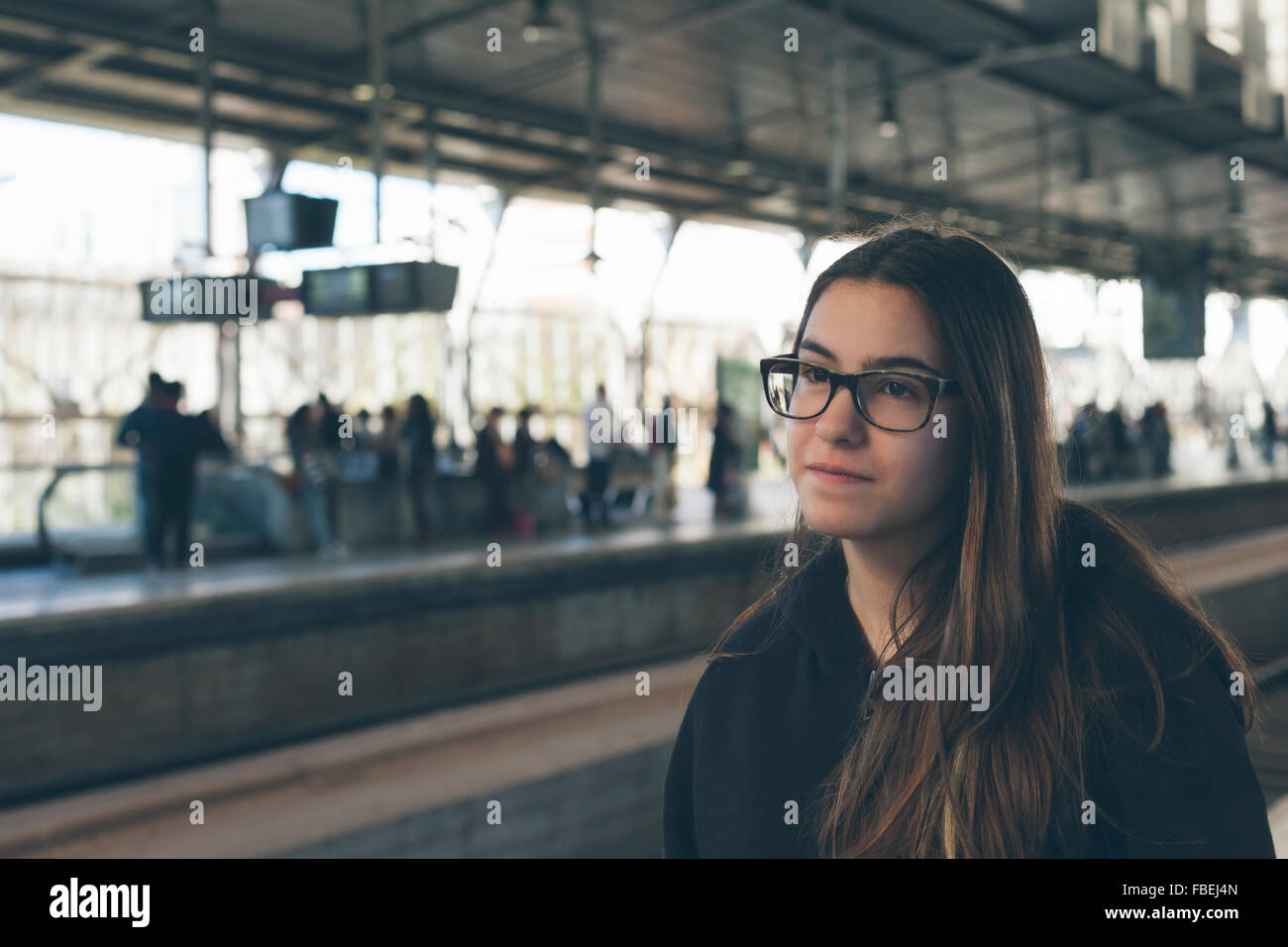 Young Woman With Eyeglasses Standing On Railroad Station - Stock Image