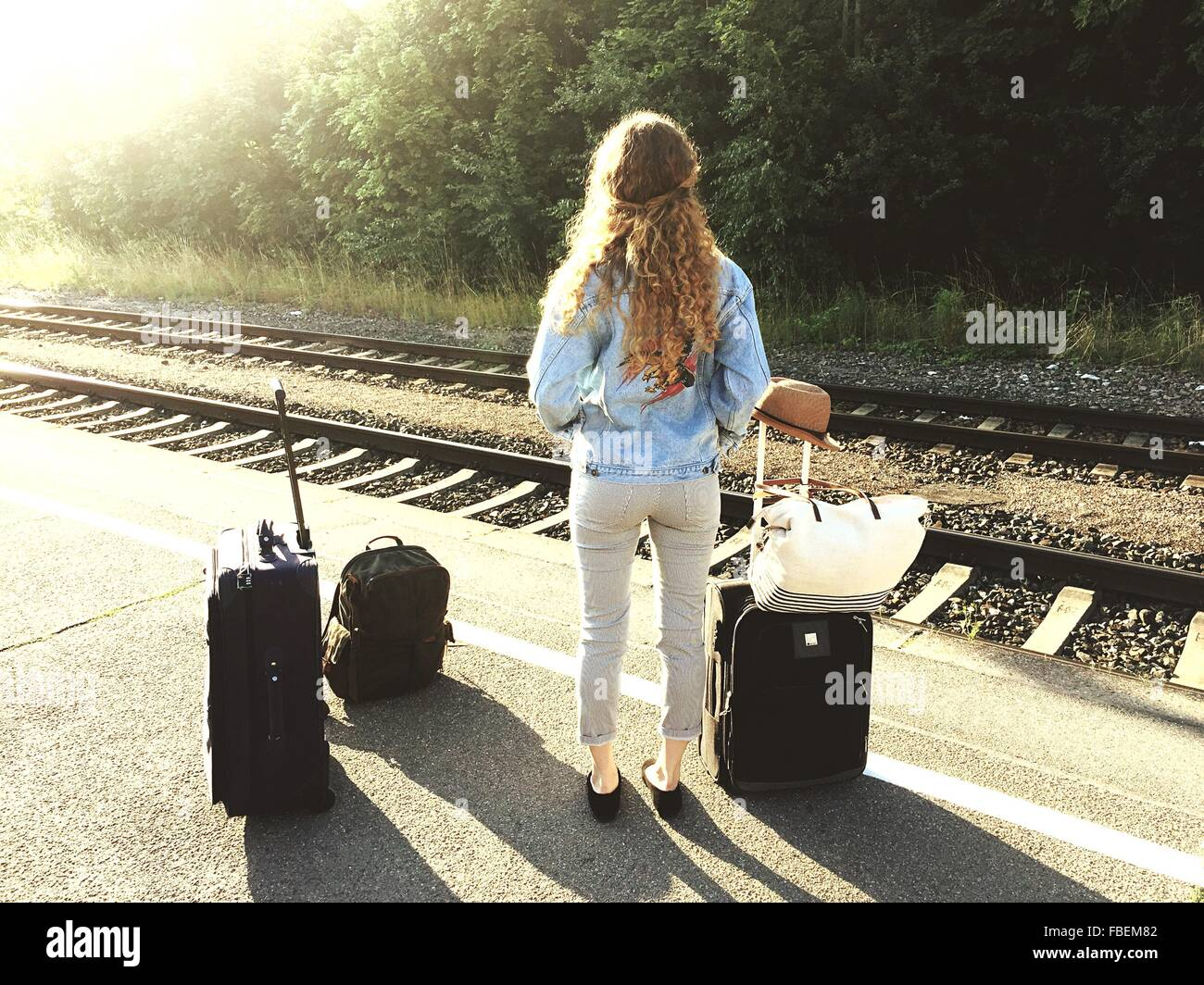 Full Length Rear View Of Woman With Luggage Standing On Railroad Station Platform - Stock Image