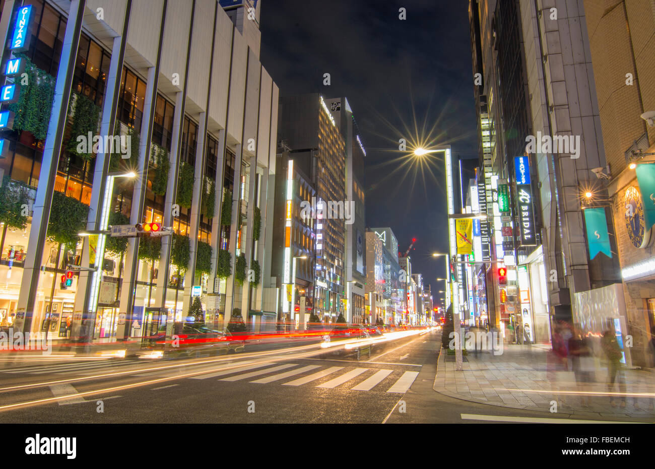 Tokyo Japan local crowds Ginza shopping twilight traffic blurs of movement on street downtown with rush of locals - Stock Image