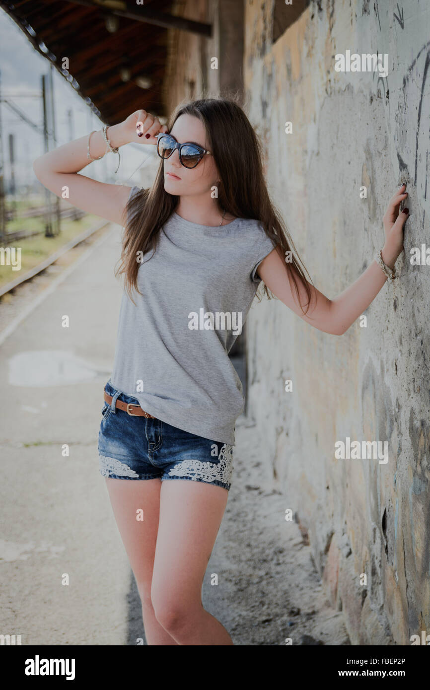 Beautiful Woman In Sunglasses Standing By Wall - Stock Image