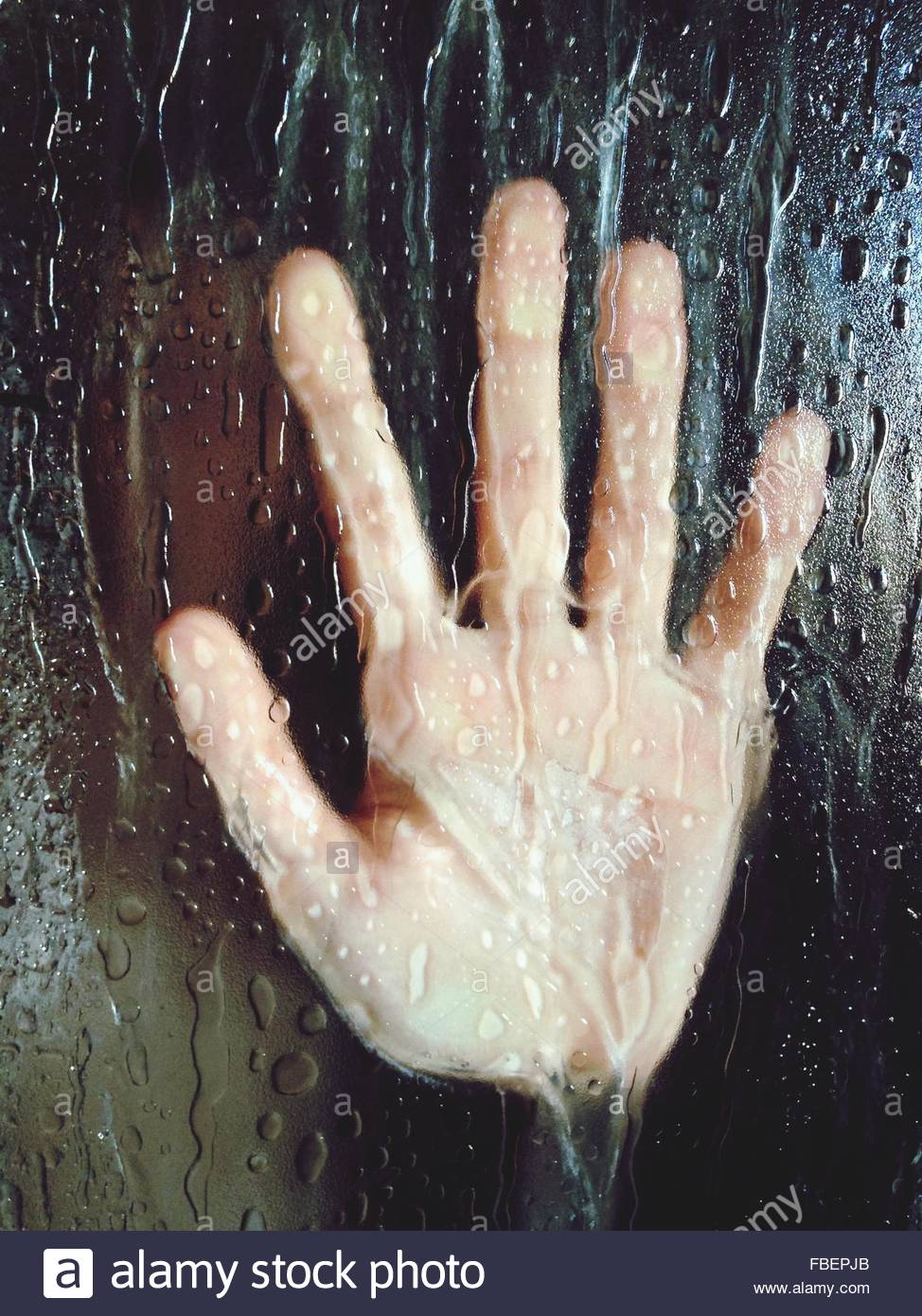 Close-Up Of Hand On Wet Glass - Stock Image