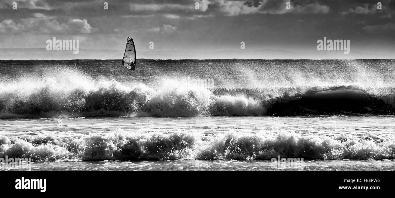 Wind surfer under sail beyond breaking surf. - Stock Image