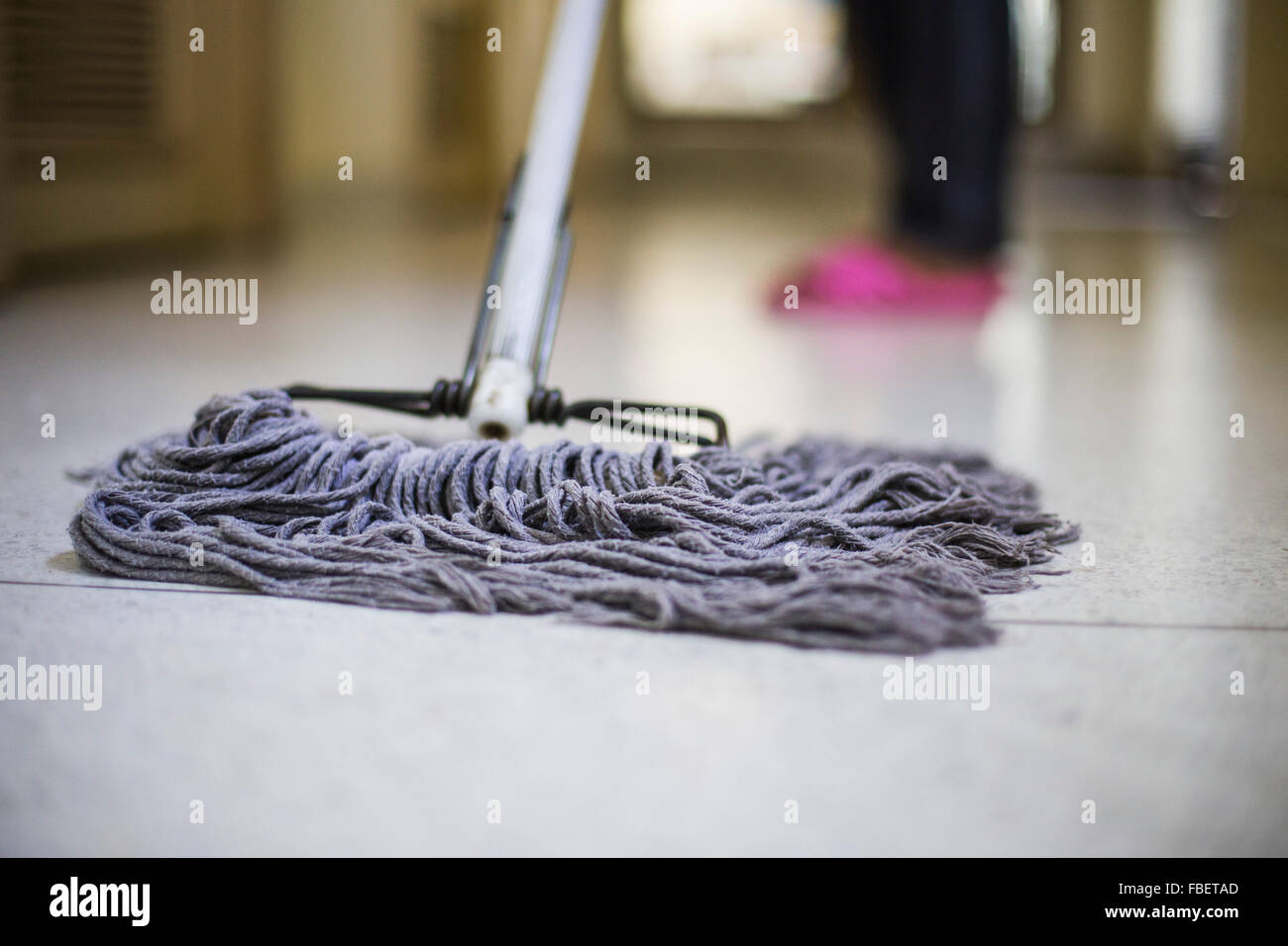 Low Section Of Person Cleaning Floor With Mop - Stock Image