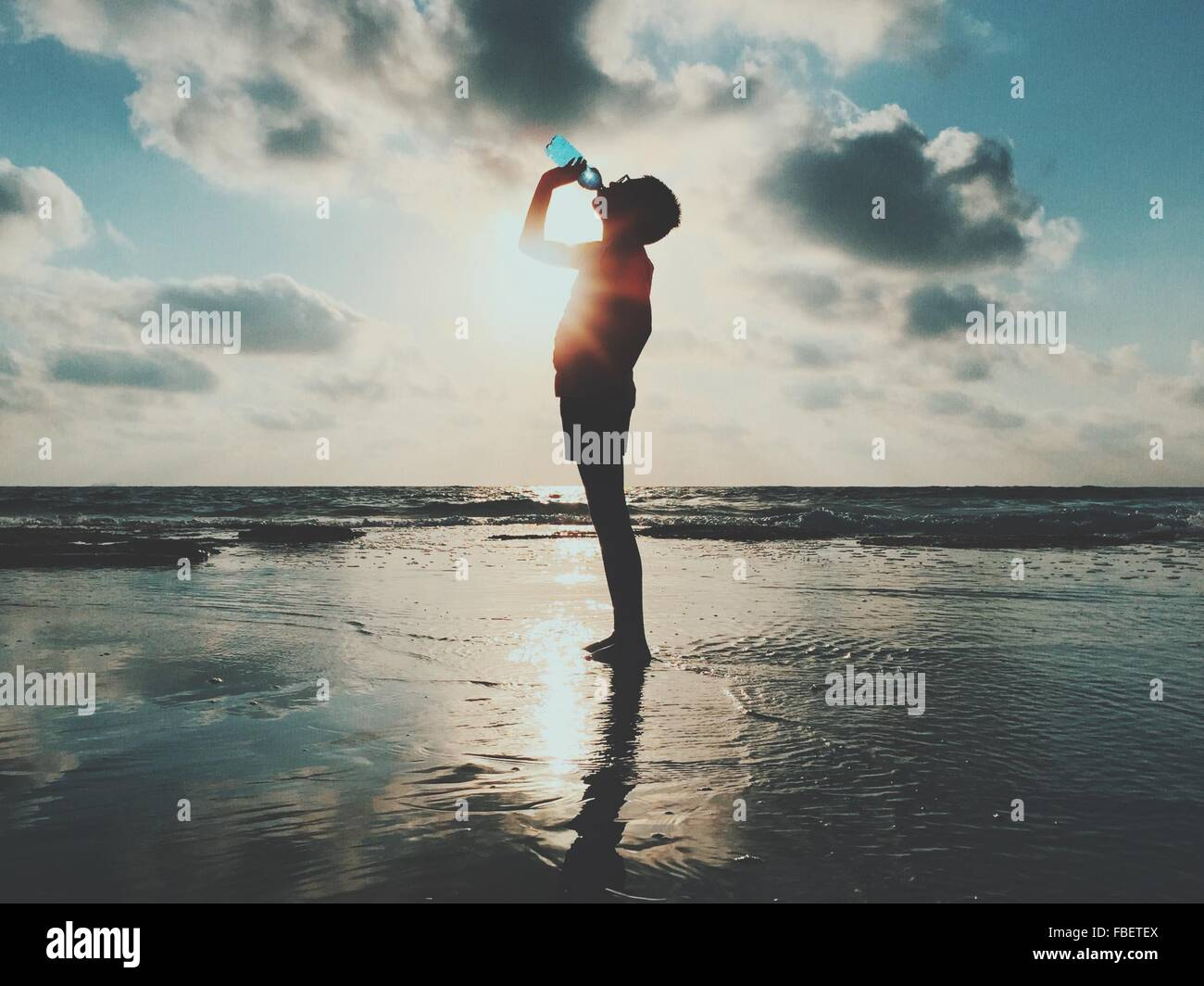 Side View Of Man Standing And Drinking Water At Sea Shore Against Cloudy Sky - Stock Image