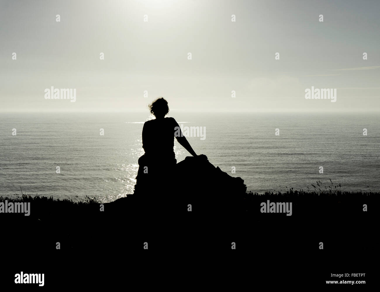 Silhouette Woman Sitting On Rock Against Sky - Stock Image