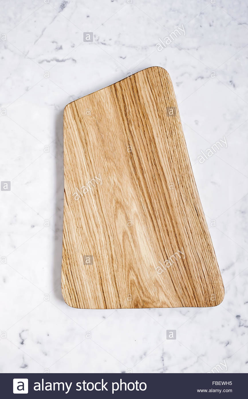 Oak cutting board with space for text on marble background, close-up - Stock Image