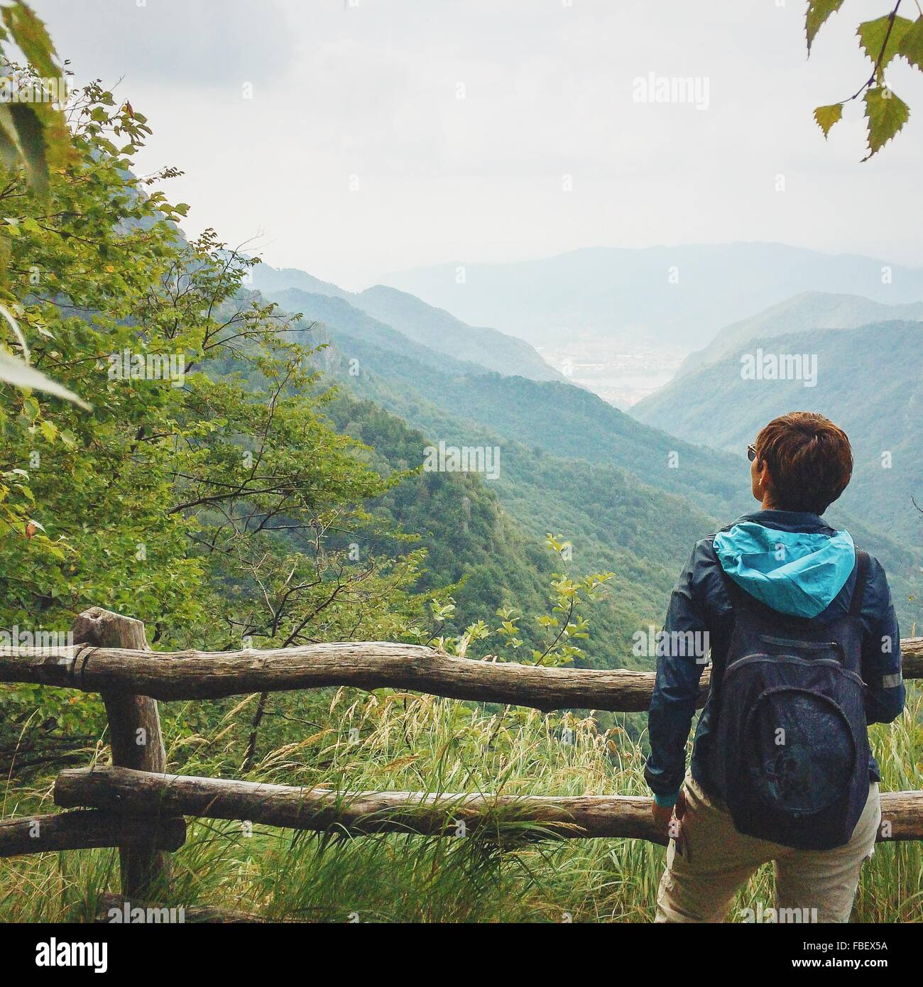 Rear View Of Man With Backpack Standing Against Mountains - Stock Image