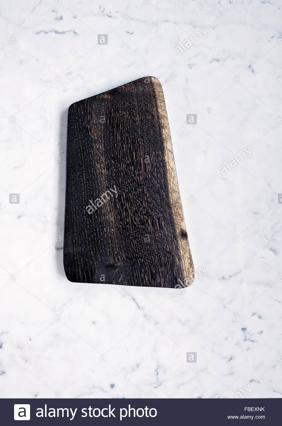 Black oak cutting board with space for text on marble background, close-up - Stock Image