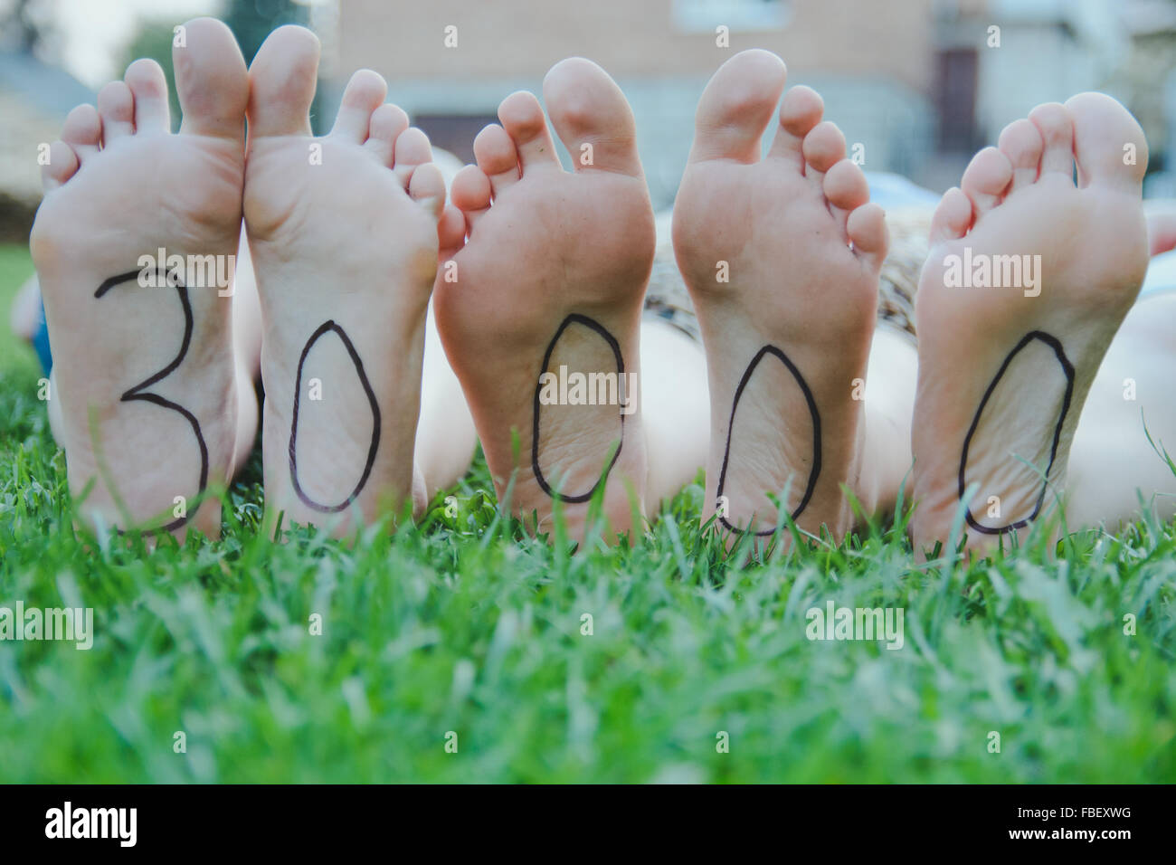 Low Section Of People With Number On Feet Lying On Field - Stock Image