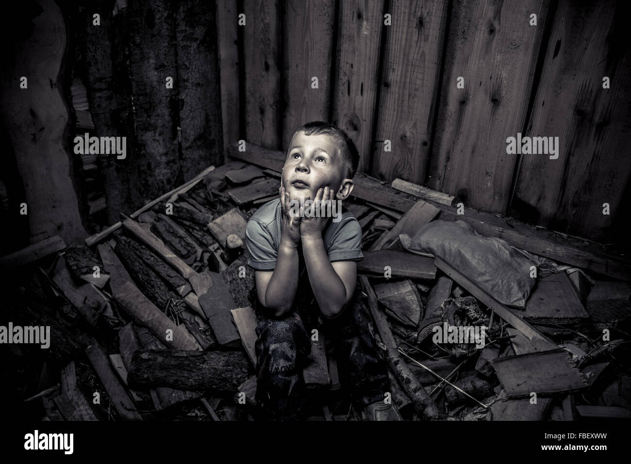 High Angle View Of Trapped Boy Sitting On Rubble In Room - Stock Image