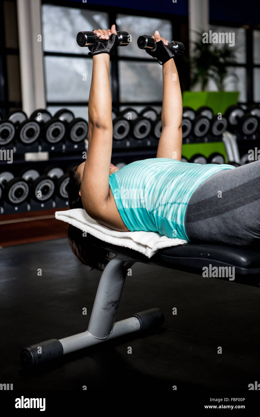 Pregnant woman lifting dumbbell - Stock Image