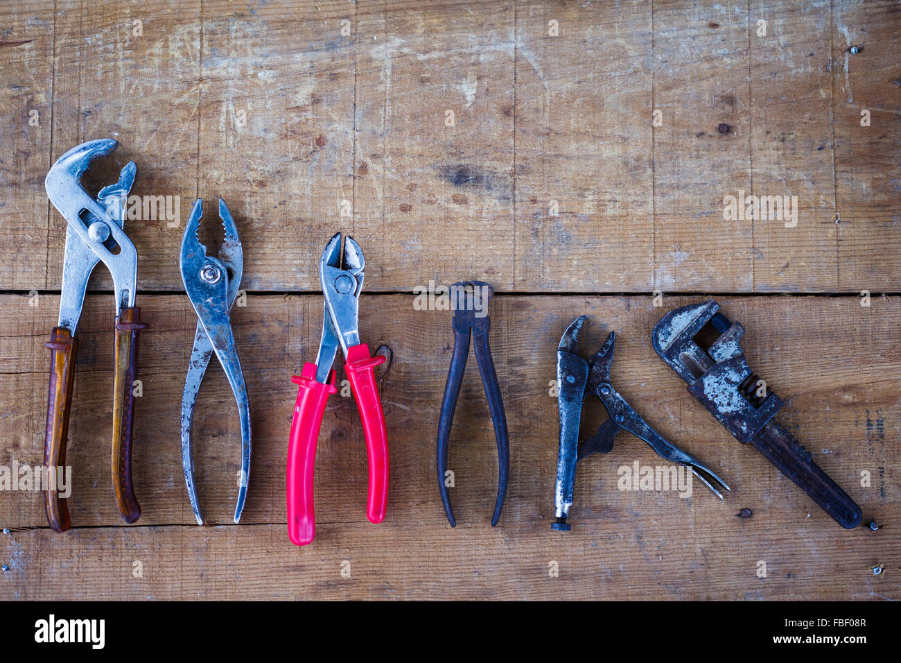 Directly Above Shot Of Various Pliers On Wooden Table - Stock Image