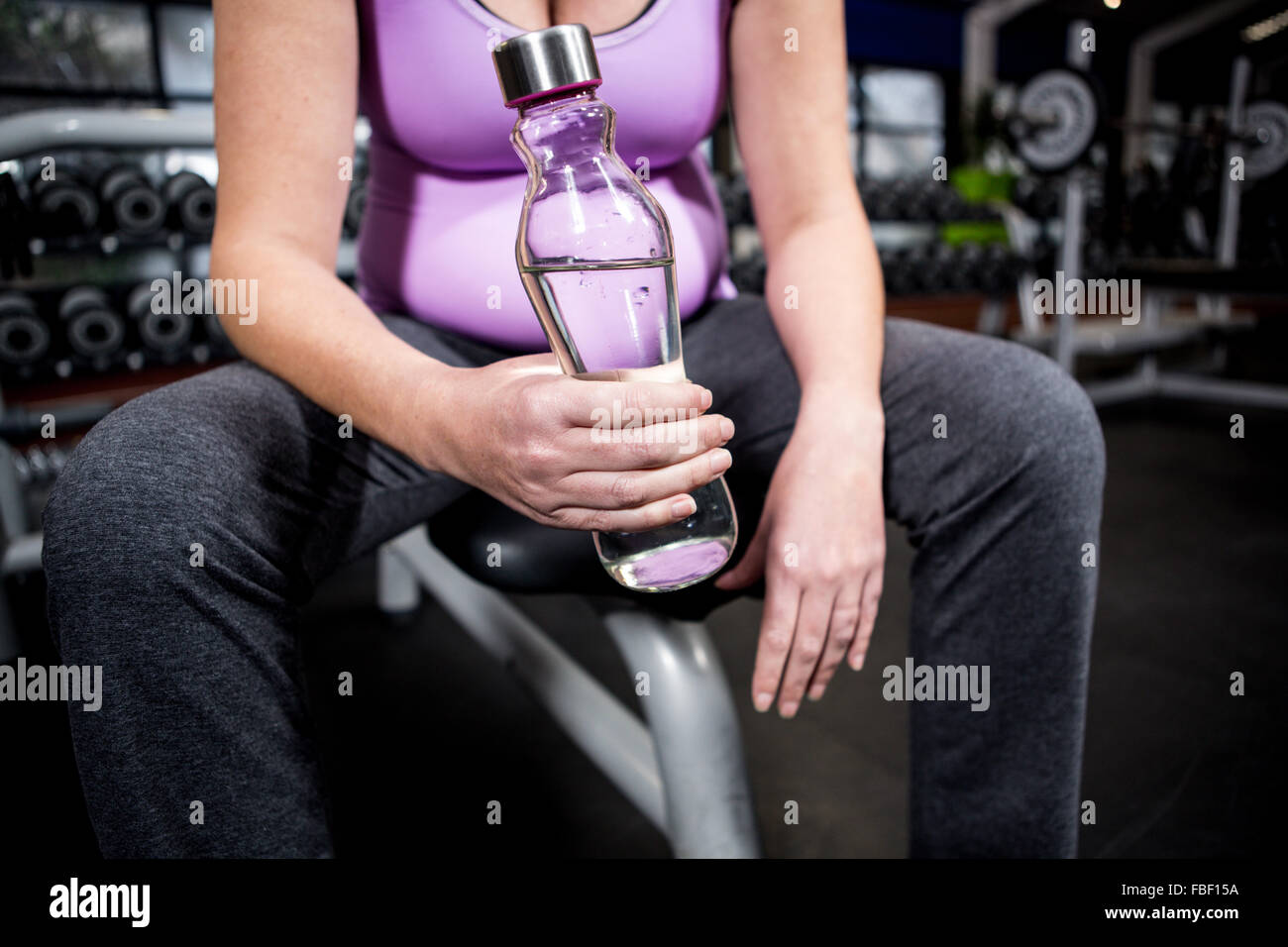 Pregnant woman holding water bottle - Stock Image
