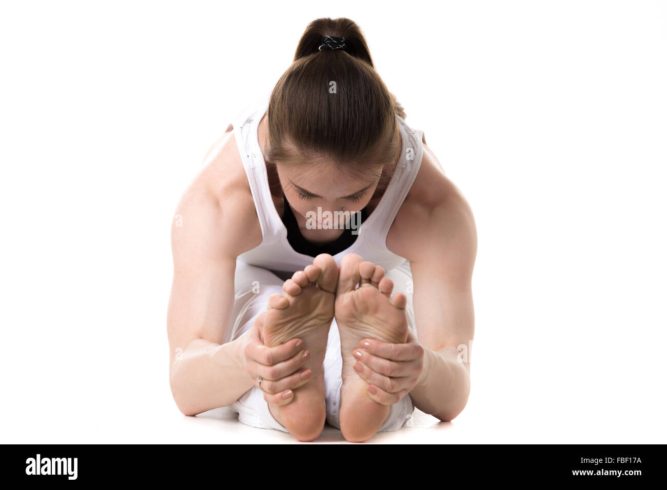 Young fitness model in white sportswear doing yoga or pilates training, seated Forward Bend pose (Intense Dorsal - Stock Image