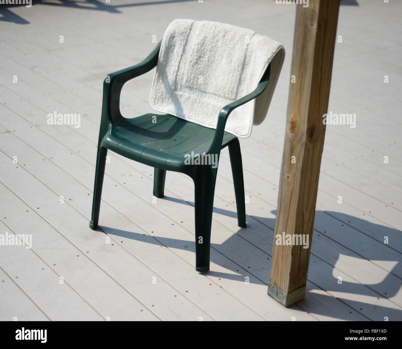High Angle View Of Towel On Plastic Chair By Wooden Post - Stock Image