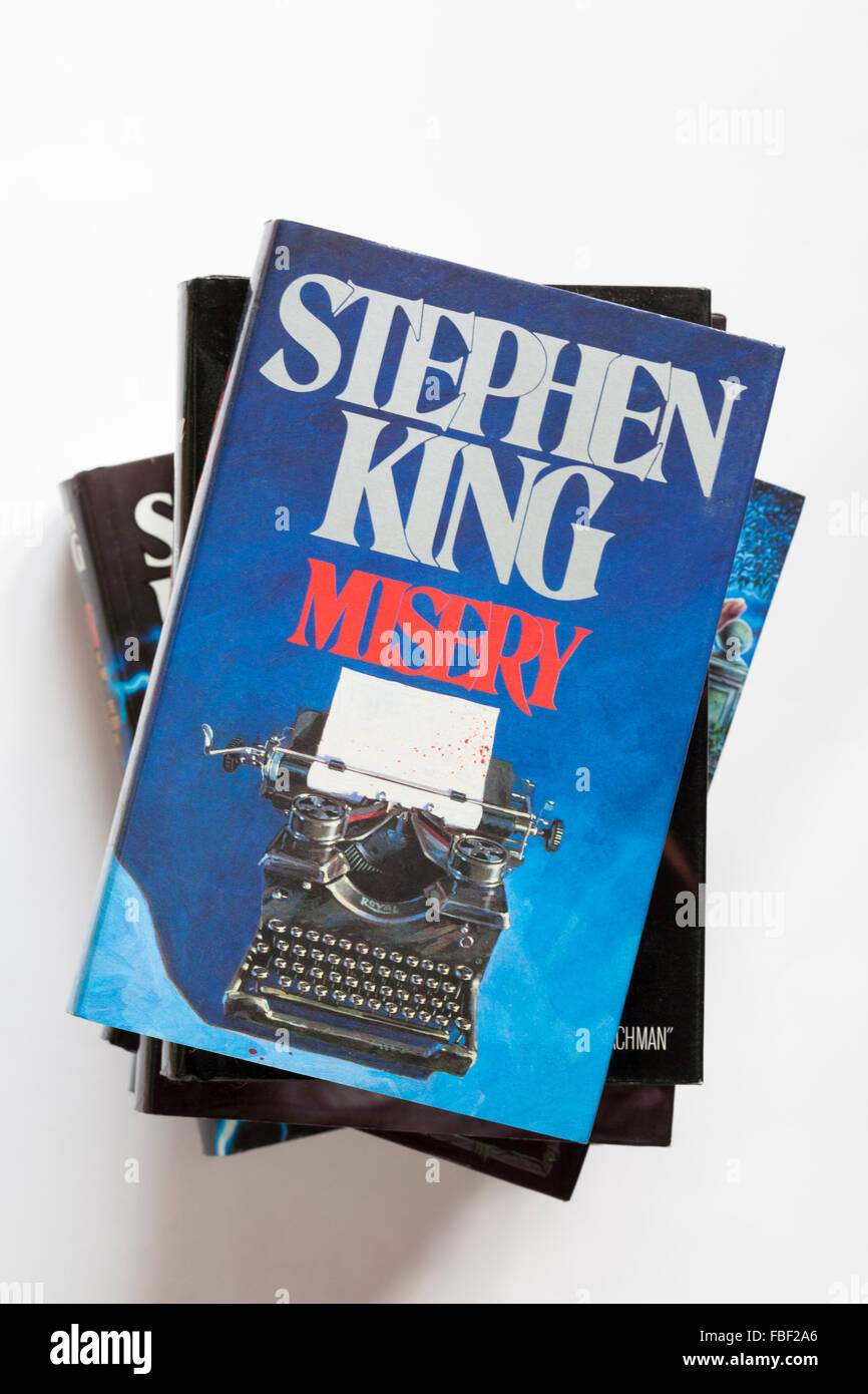 Pile of Stephen King books with Misery on top isolated on white background - Stock Image