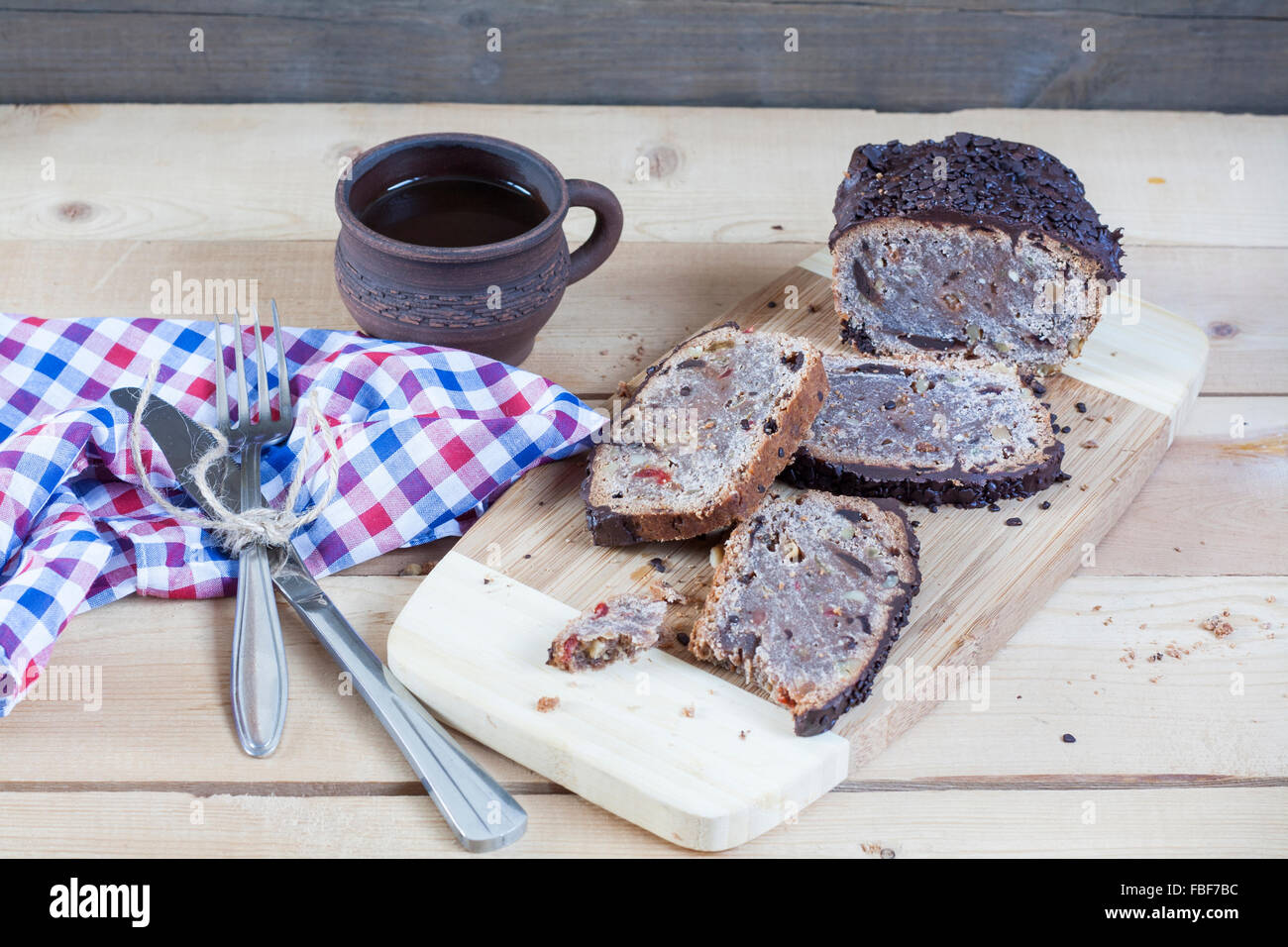 Stollen traditional German Christmas yeast cake with raisins served with a cup of coffee decorated with tablecloth - Stock Image